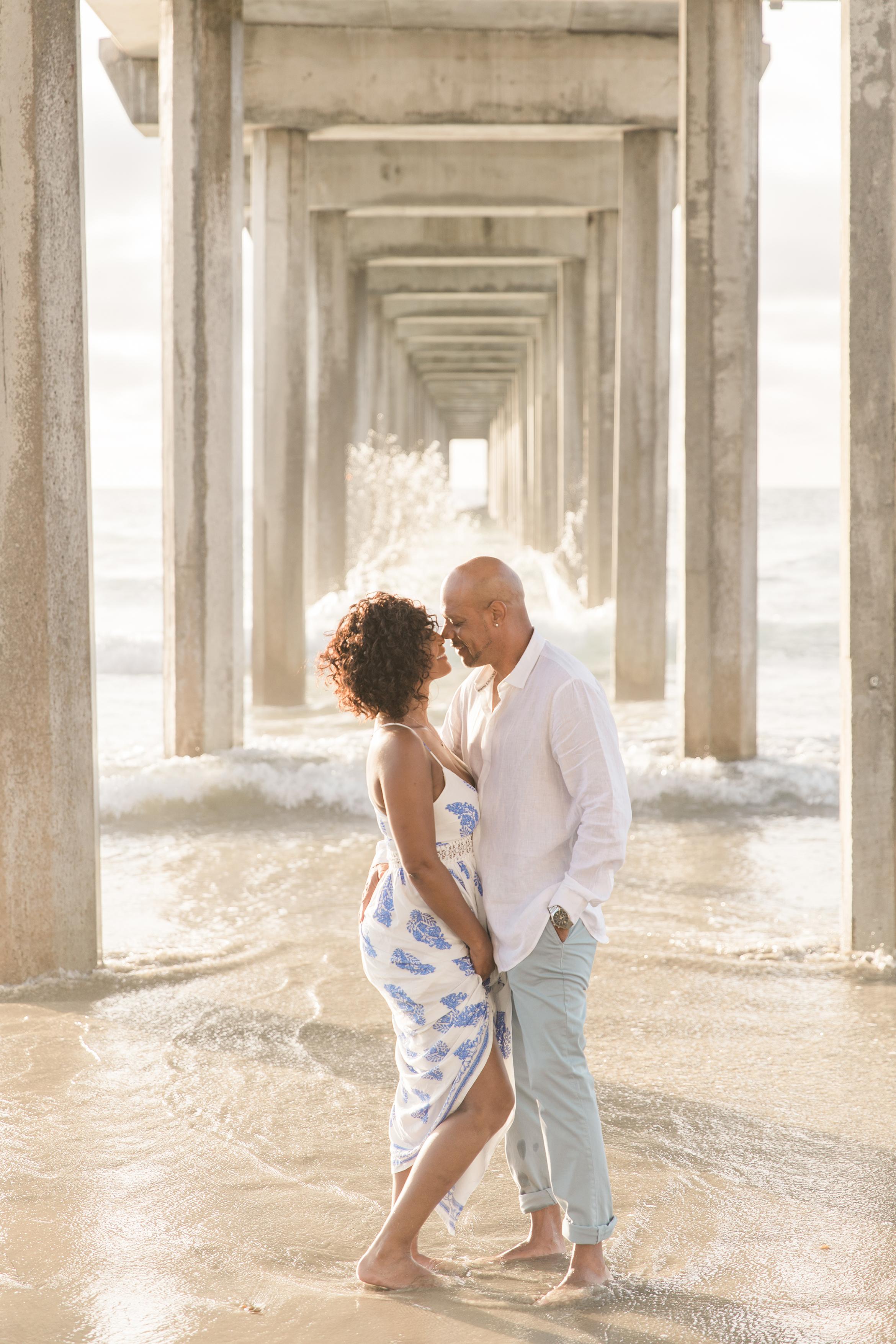 couple under beach boardwalk engagement photo