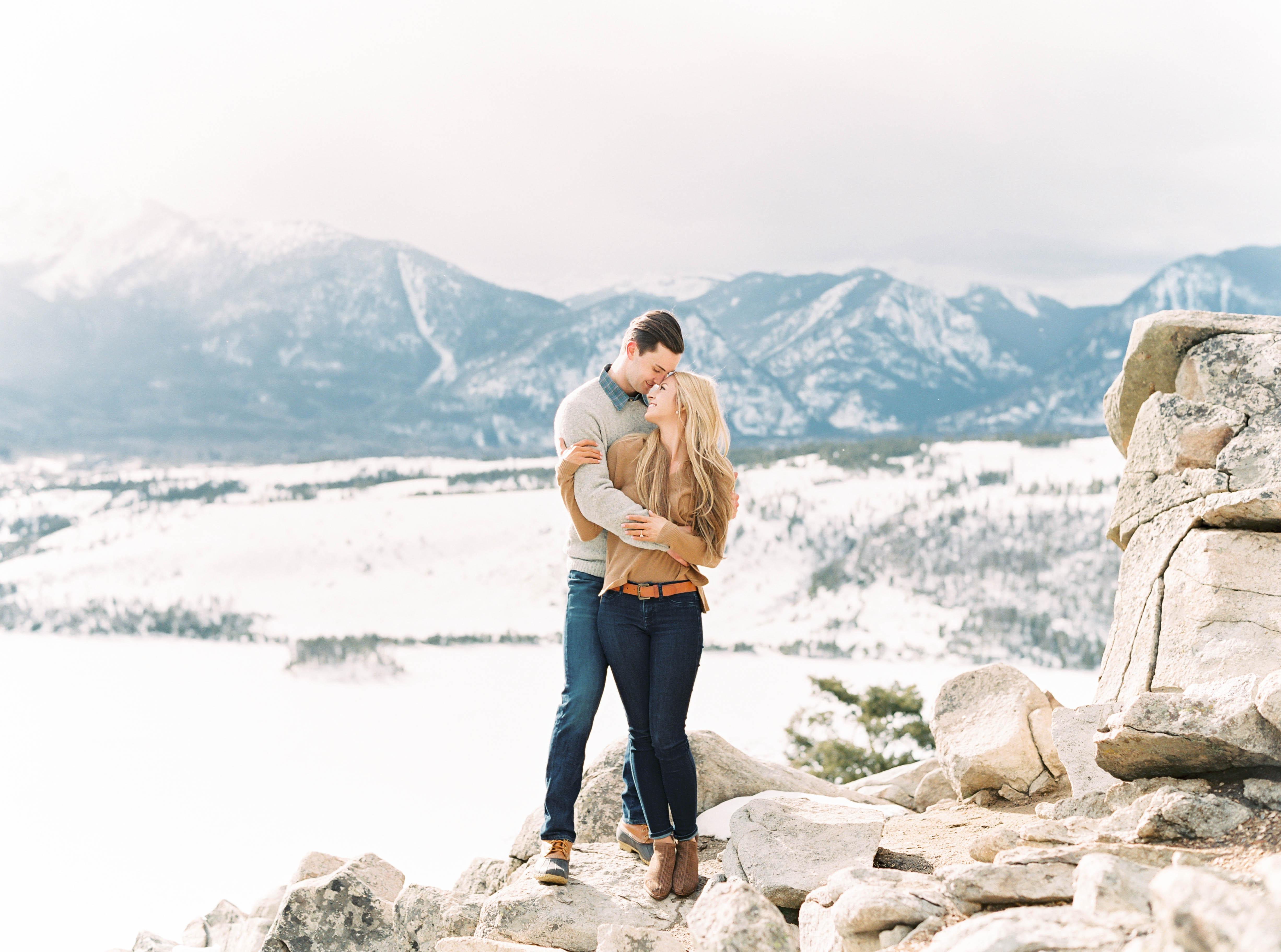destination engagement couple snow capped mountain background