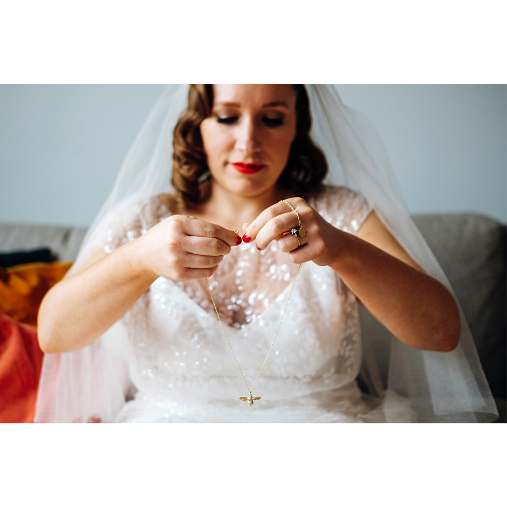 bee wedding ideas bride putting on bee necklace