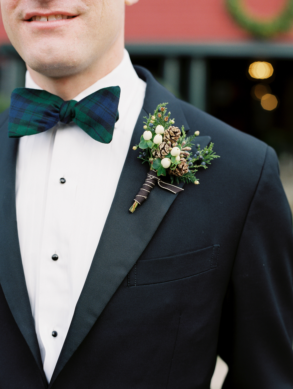 winter wedding guest attire plaid bow tie and pine cone boutonniere