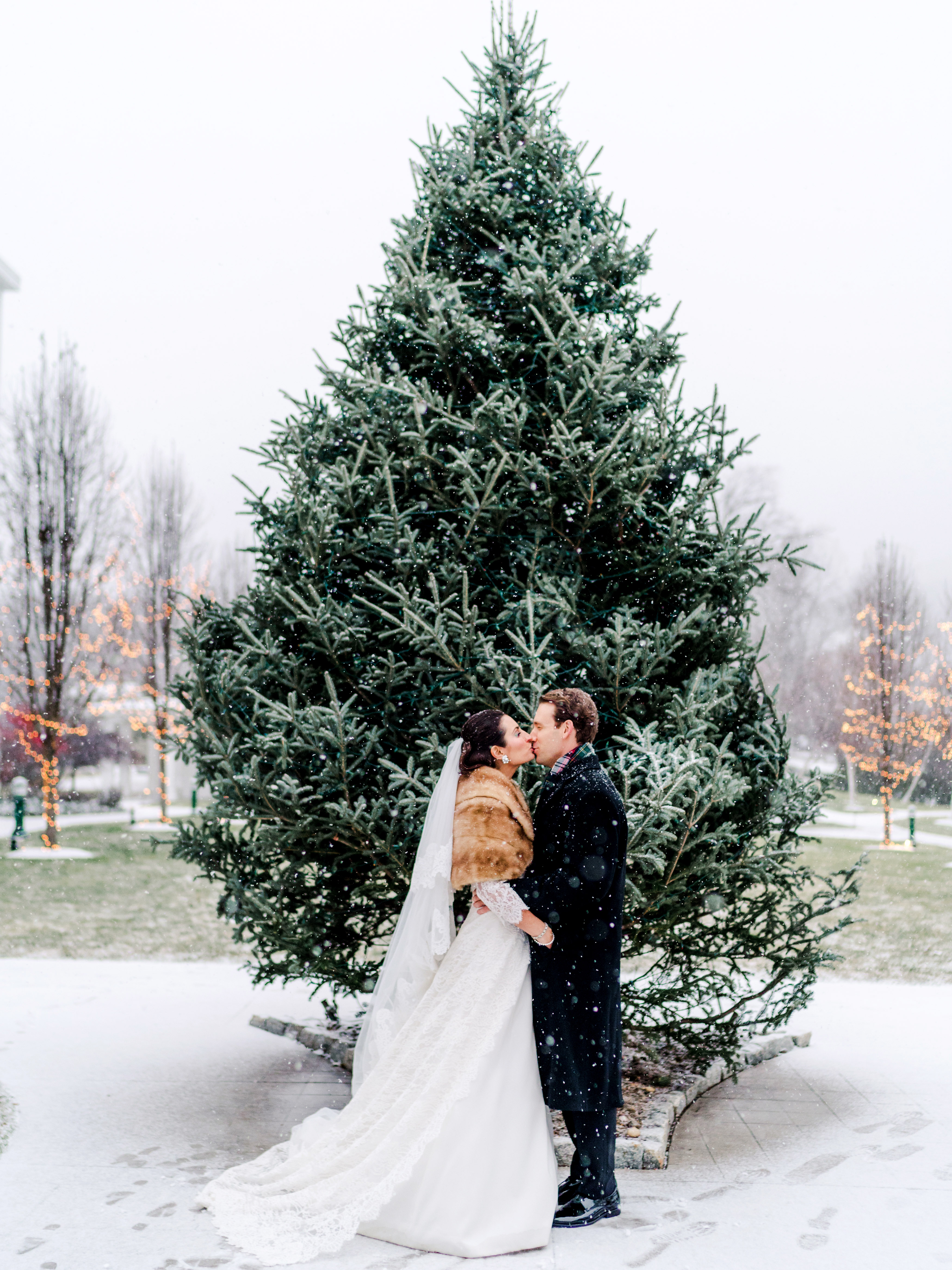 lauren christian christmas wedding couple outside kissing evergreen tree snowing