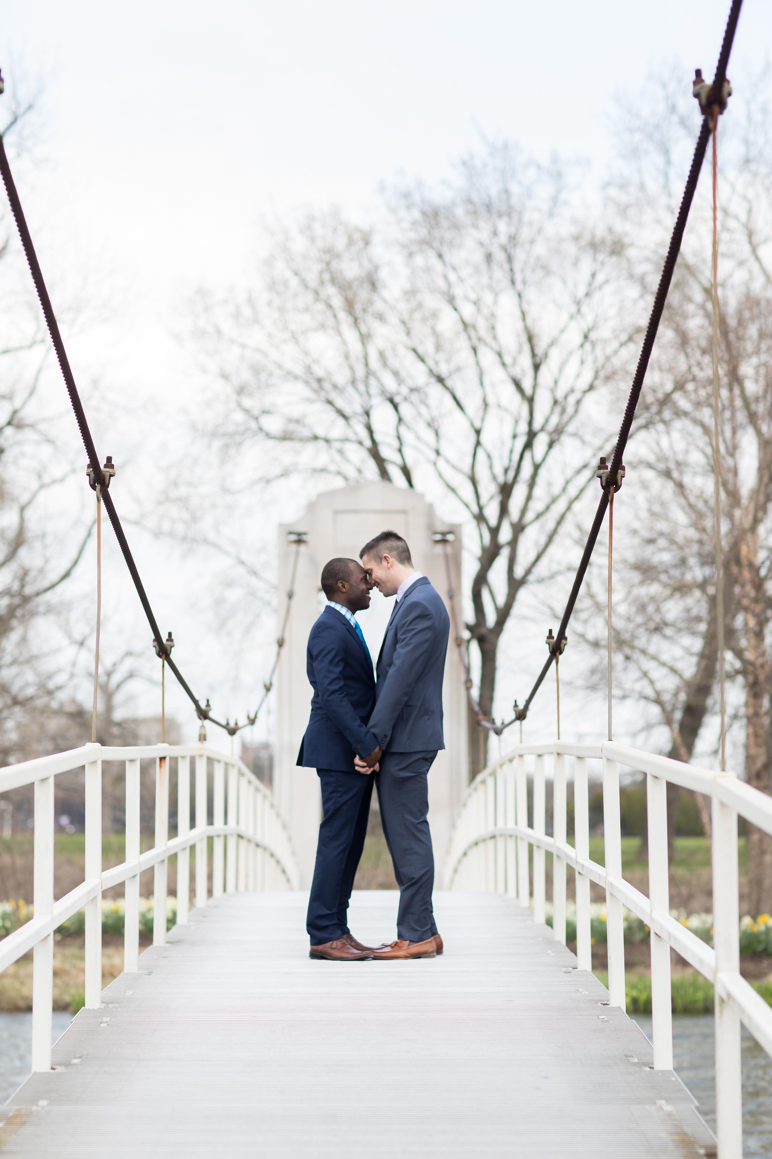 couple embrace on bridge engagement