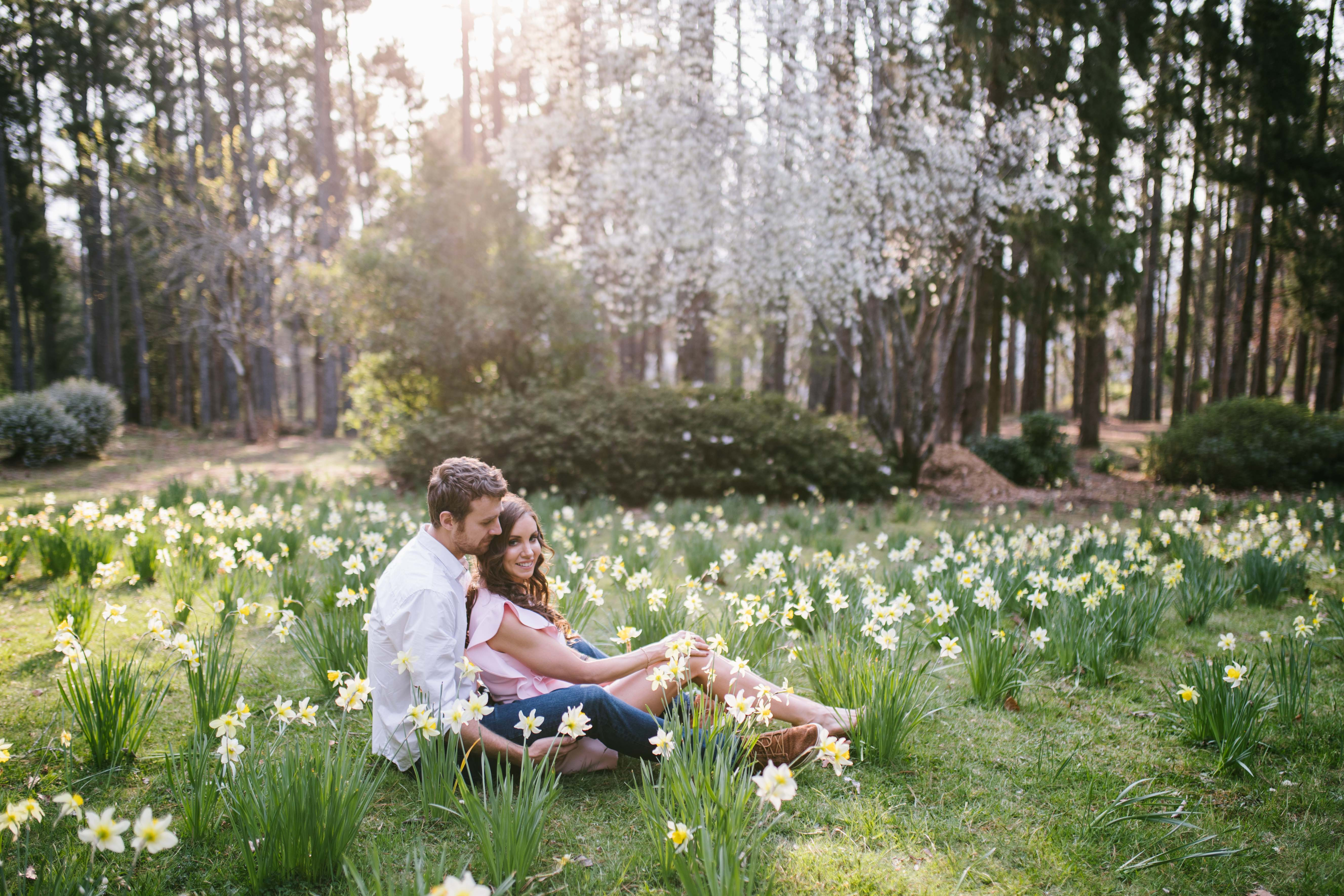 couple sitting in flower fields engagement