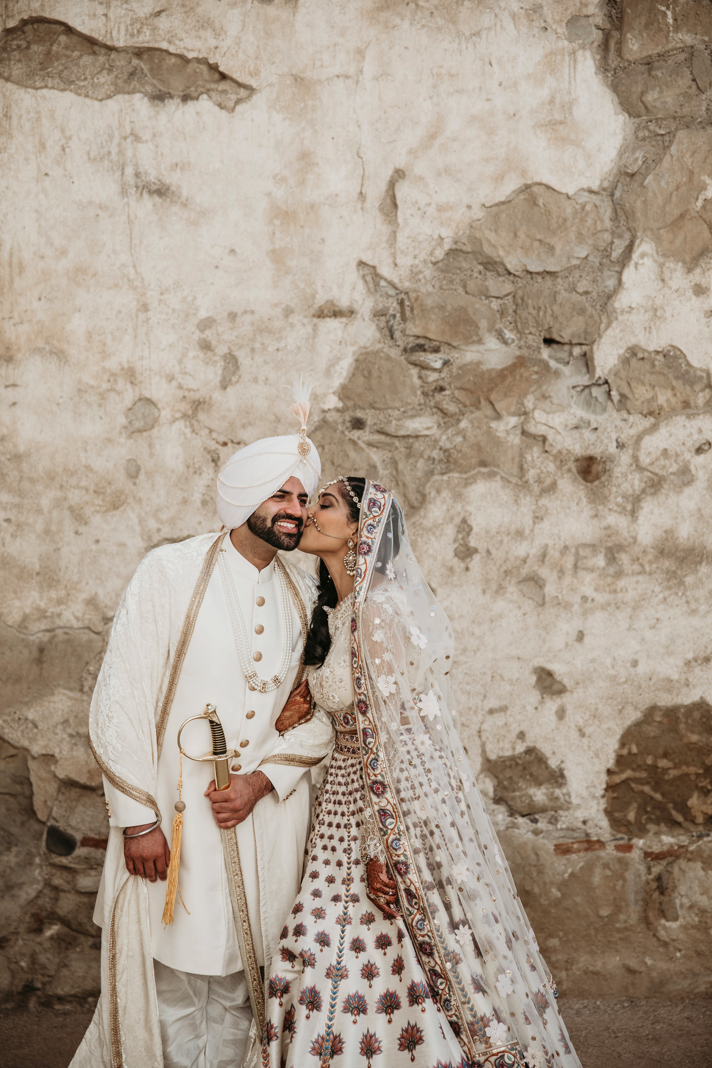 indian wedding couple bride kissing grooms cheek