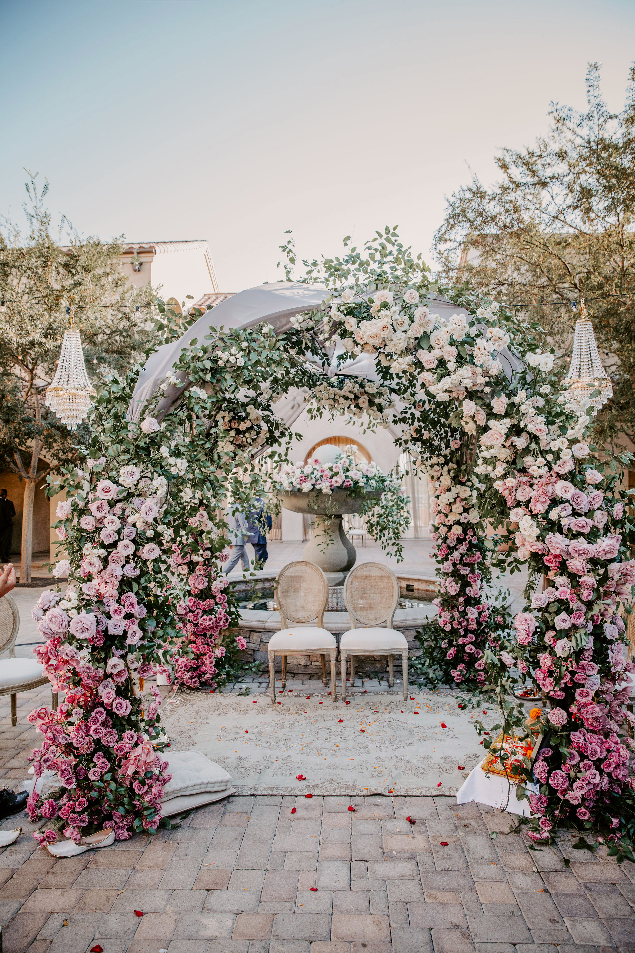 wedding floral arch two chairs in front of fountain