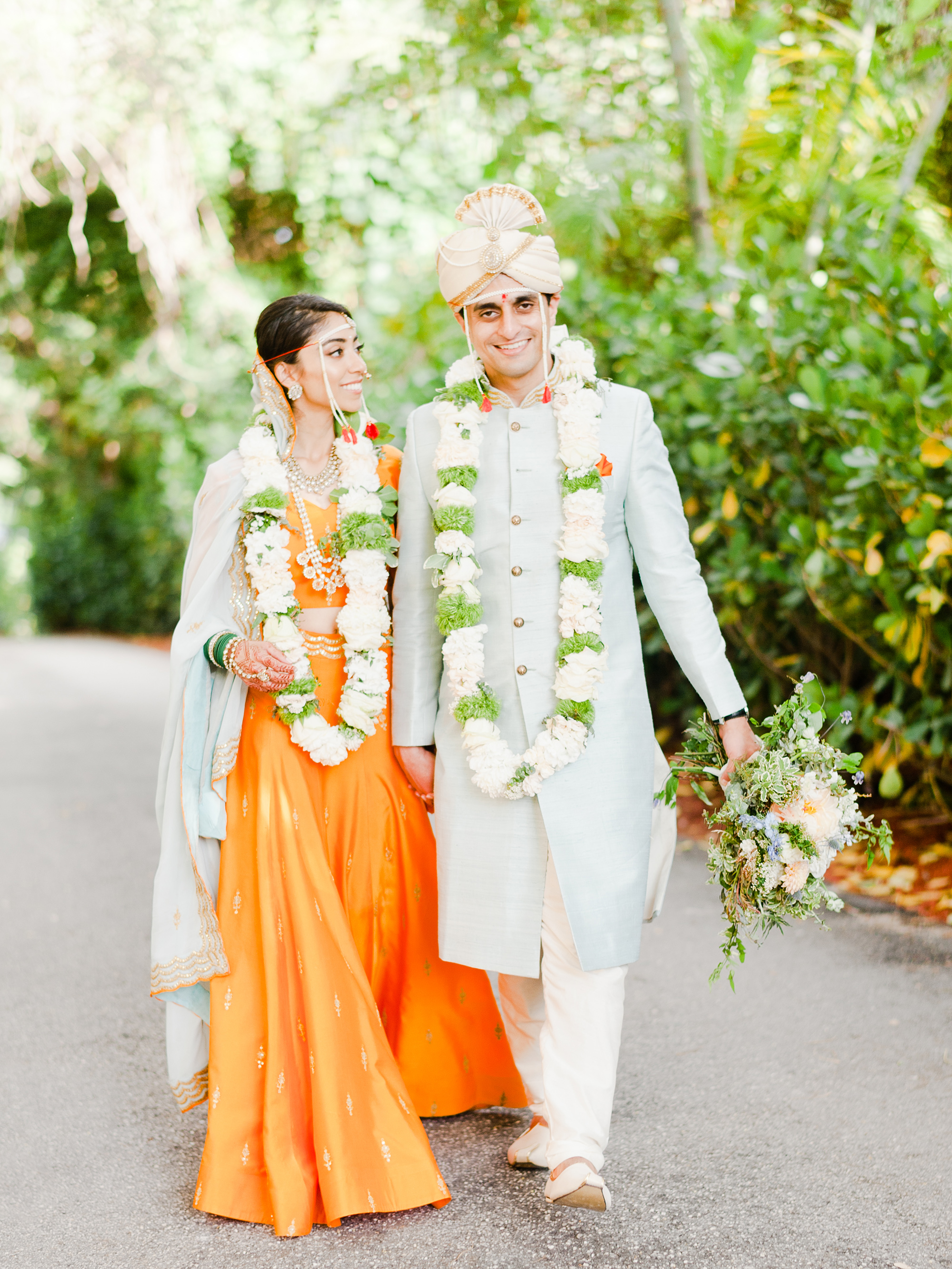 anuja nikhil wedding ceremony couple walking bride orange dress