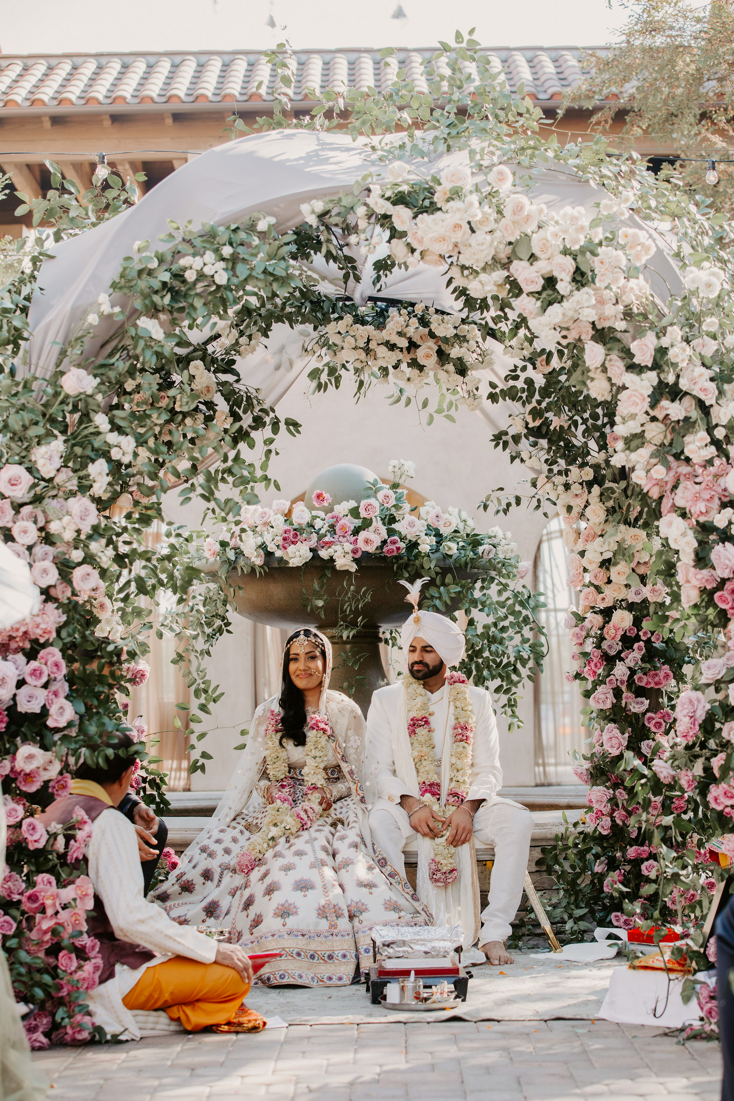indian wedding bride groom sitting below floral arch