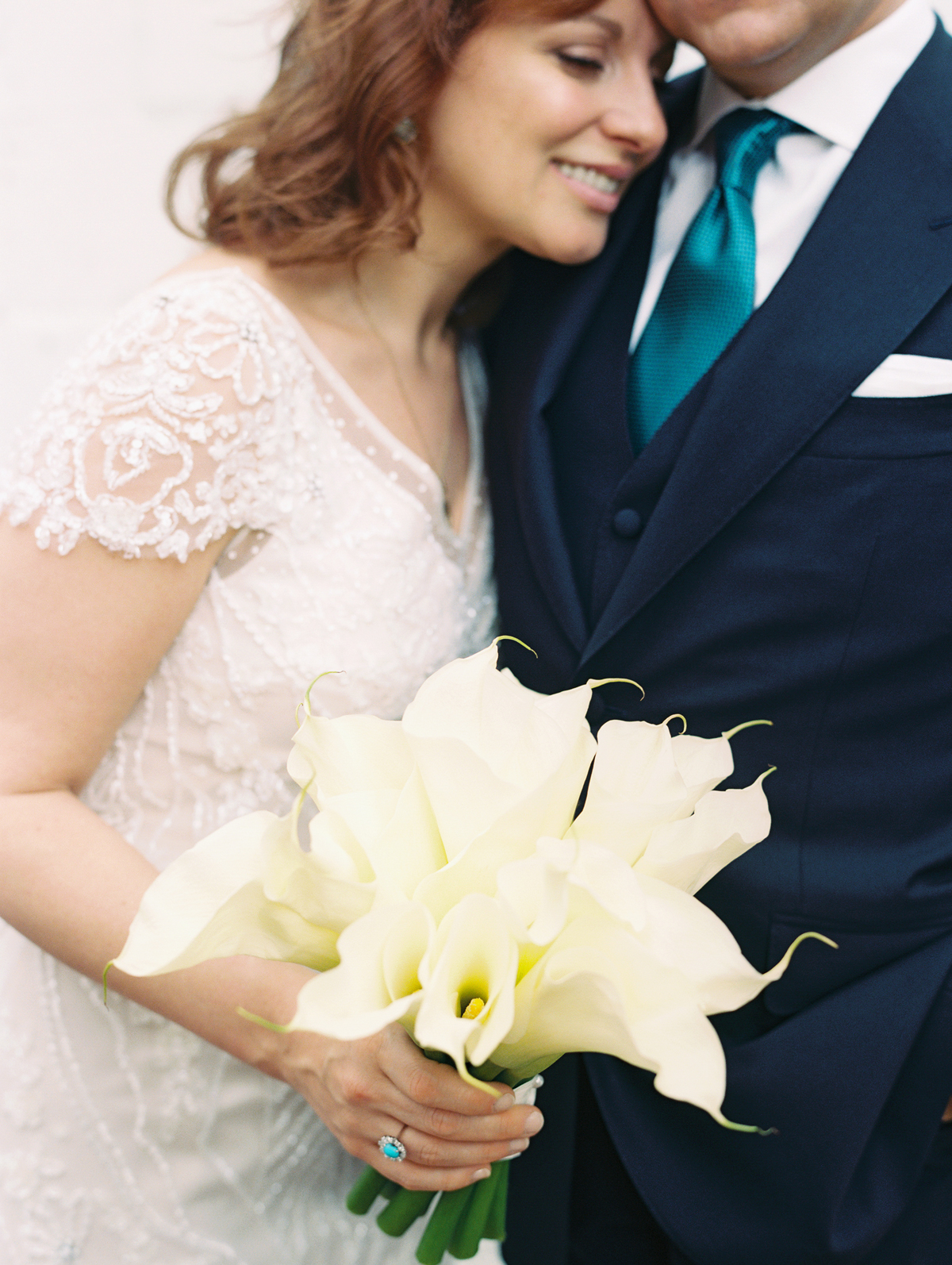 single flower wedding bouquet calla lilies held by bride embracing groom