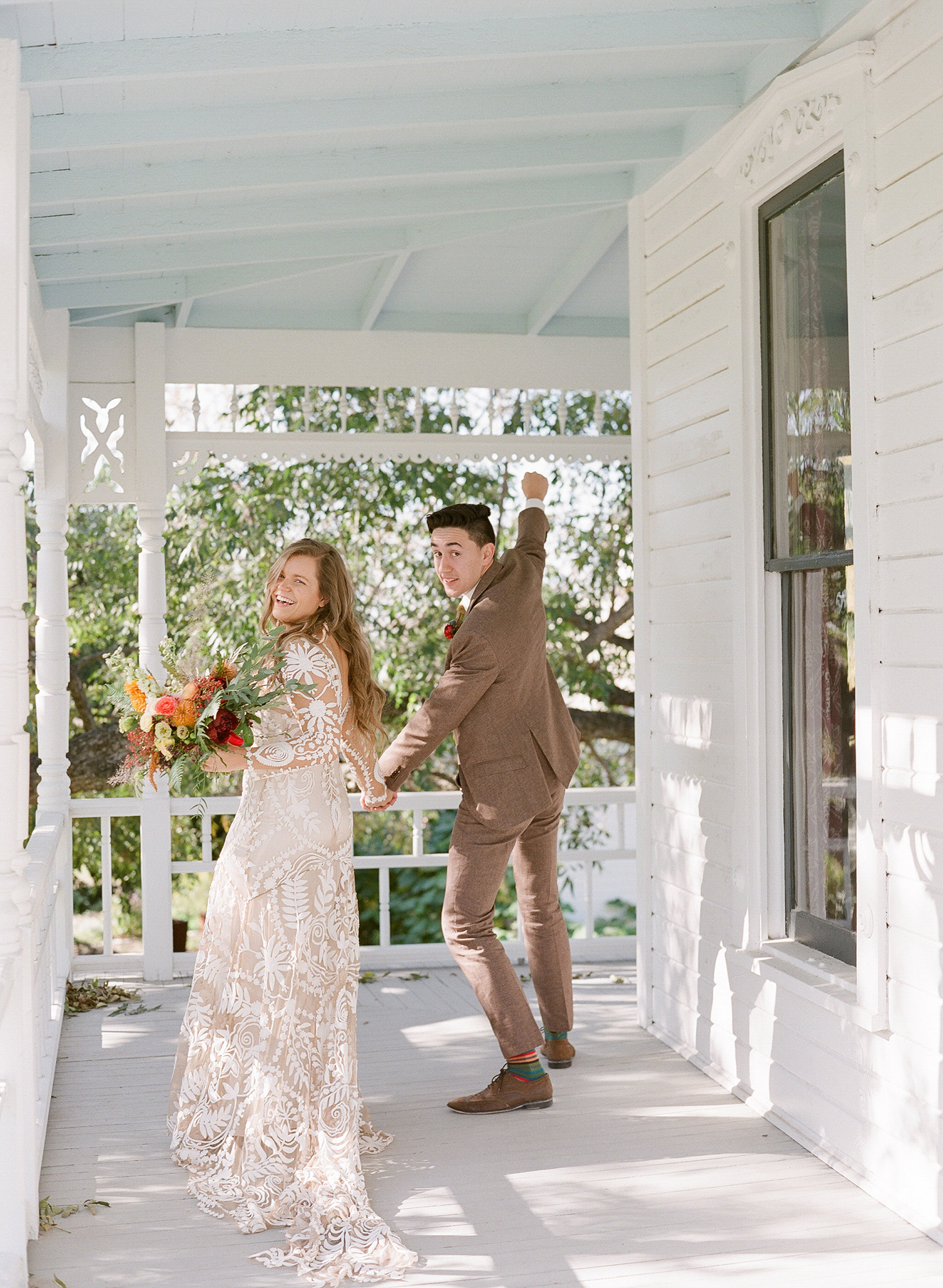 wedding couple on porch holding hands
