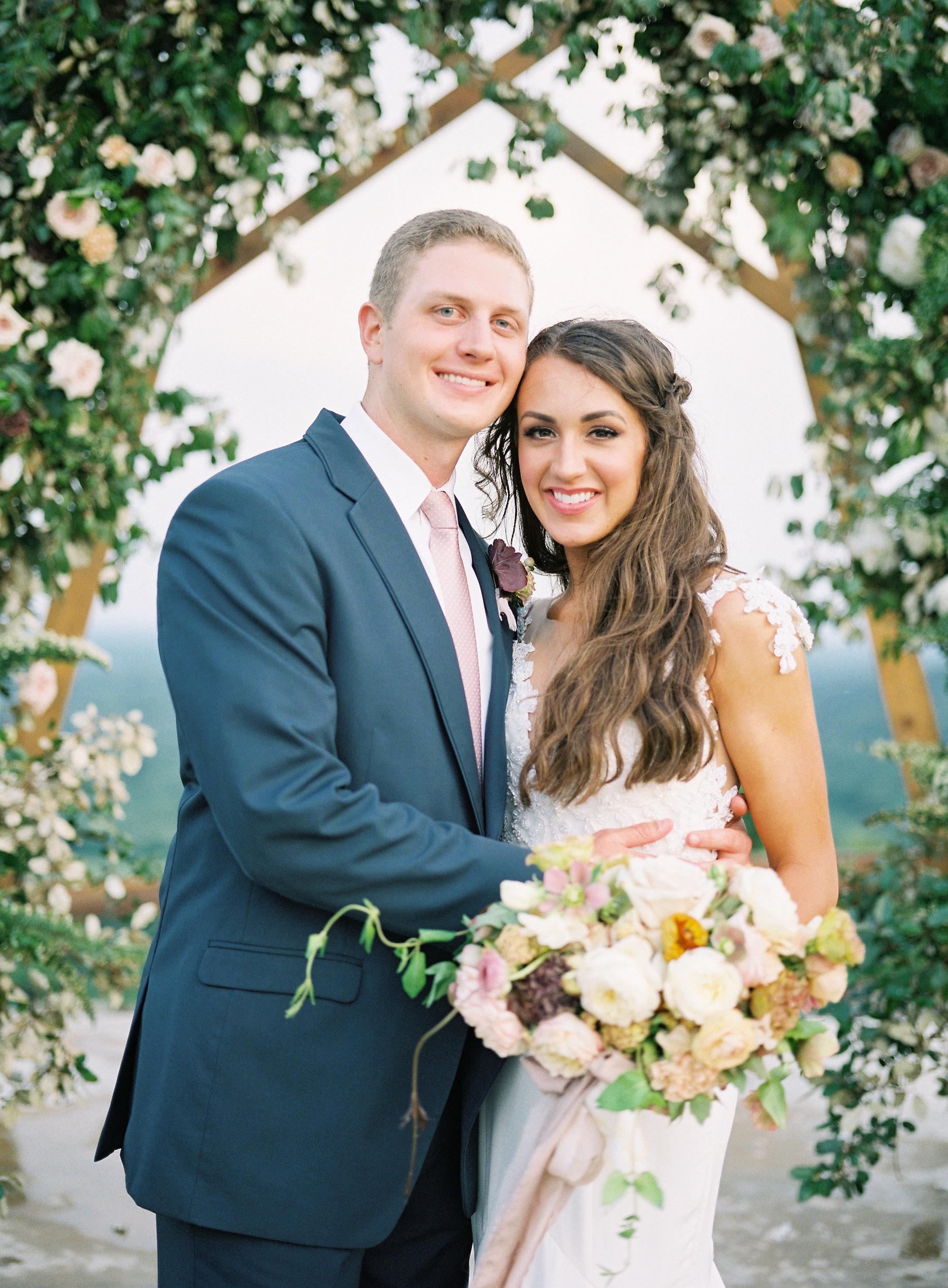 happy wedding couple pose under floral archway