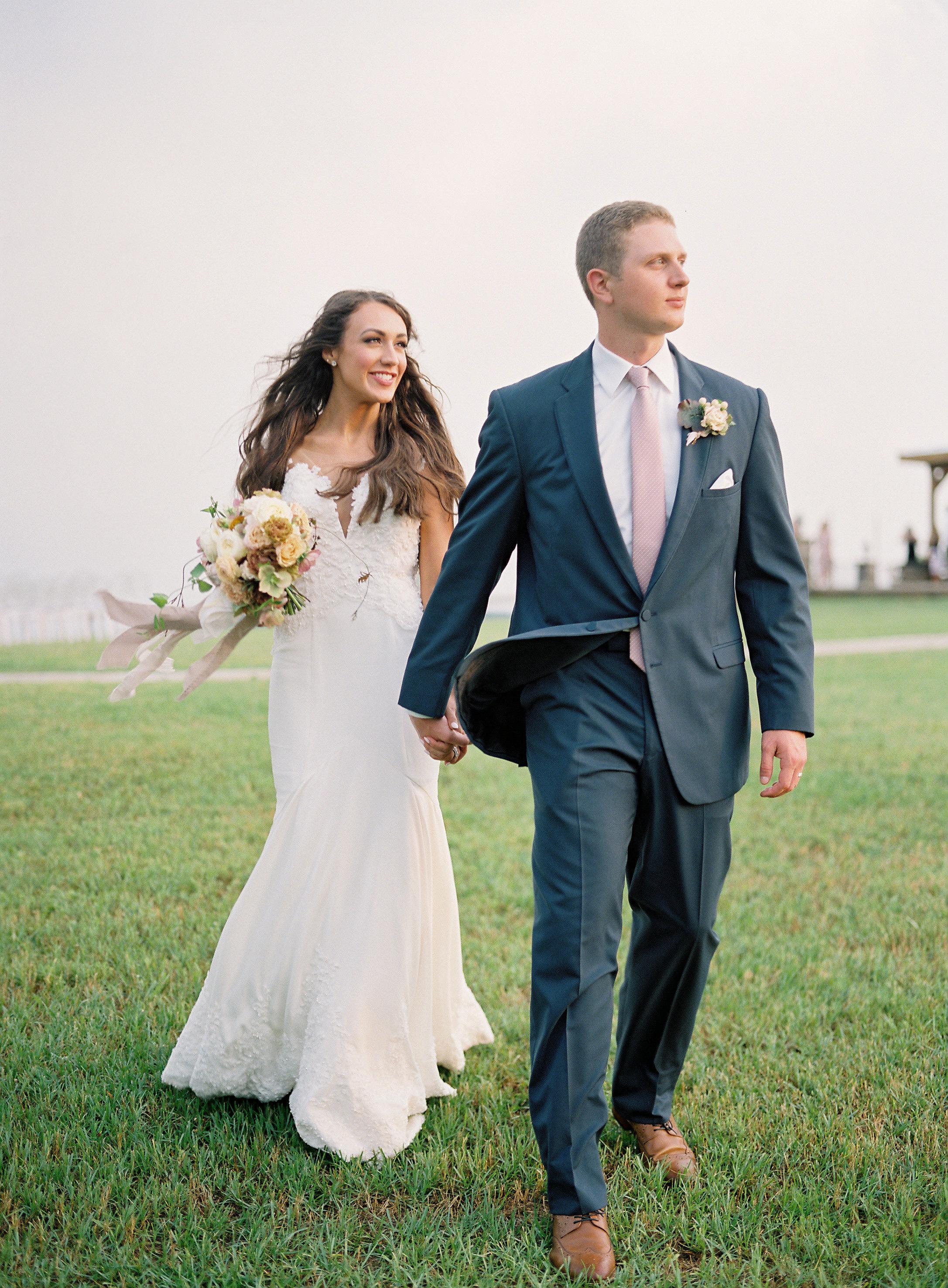wedding couple walk outdoors holding hands