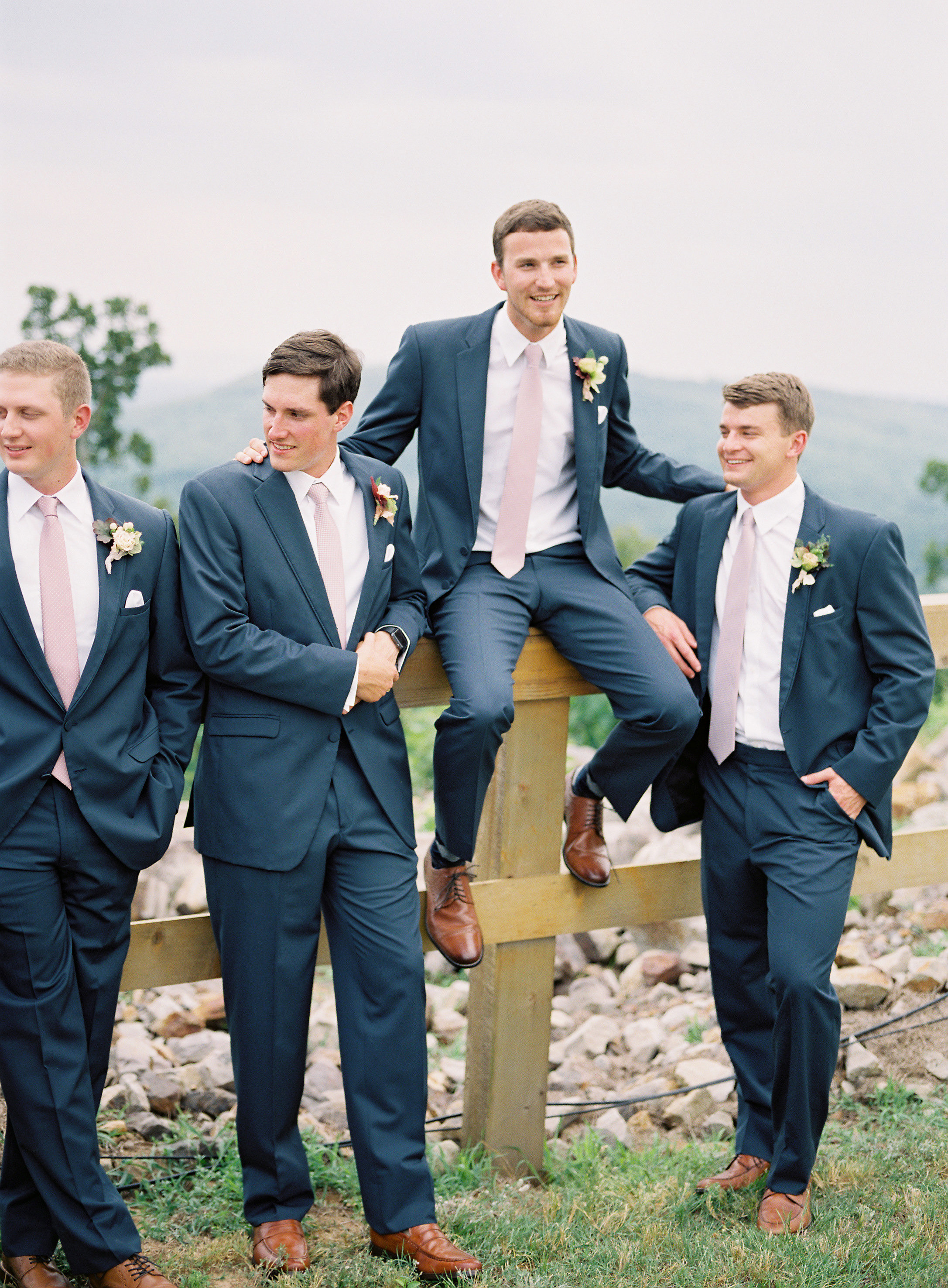 groom outdoors fence with groomsmen