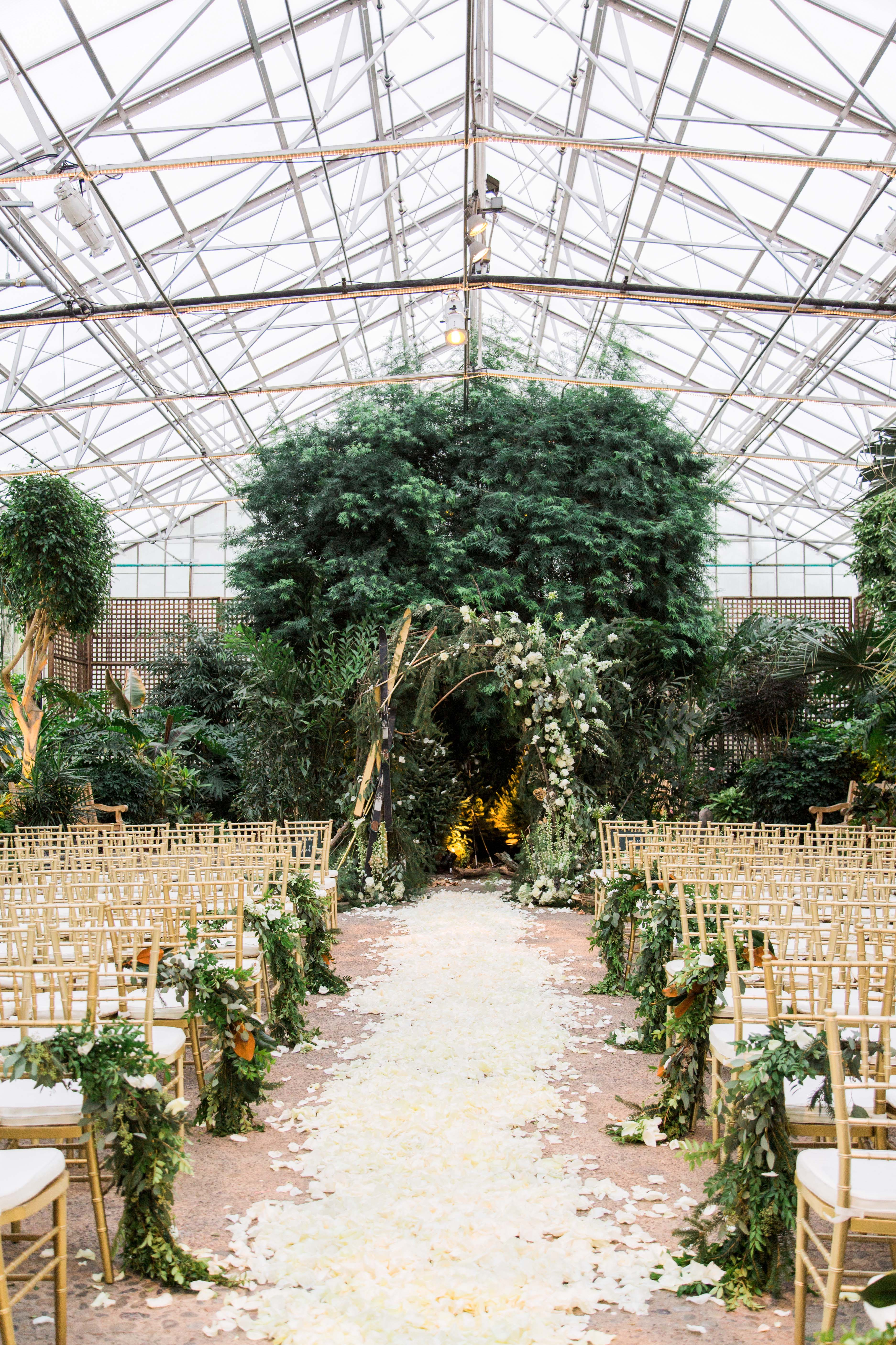 wedding ceremony greenhouse venue white flowers and greenery