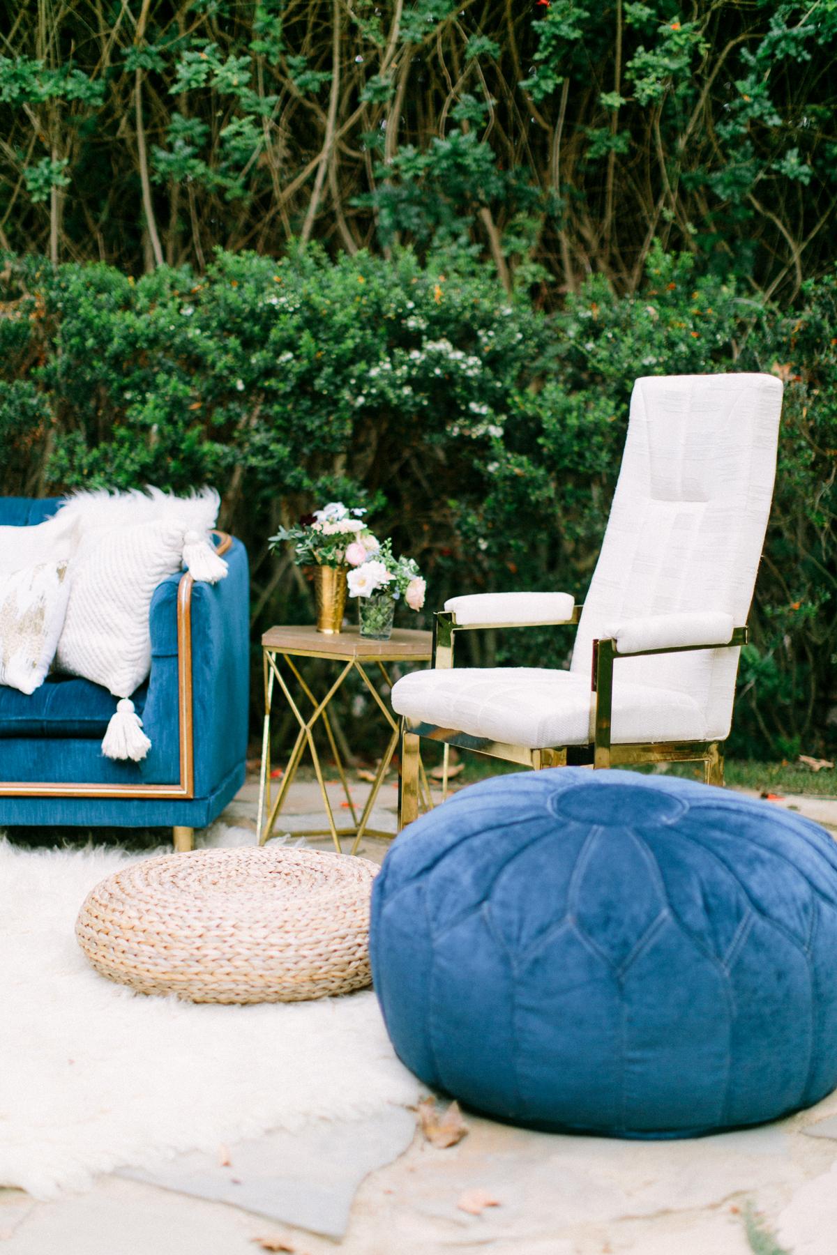 woven rattan wedding decor ottoman atop white fur rug at outdoor lounge area
