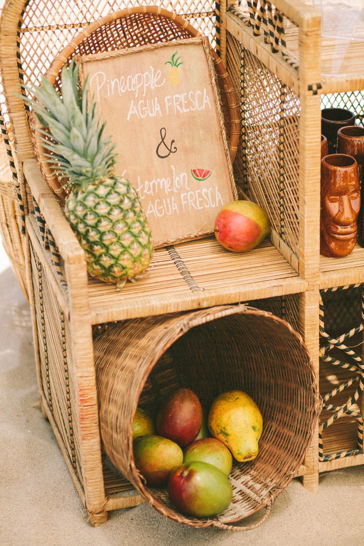 woven rattan wedding decor shelves with titki glasses and fruit