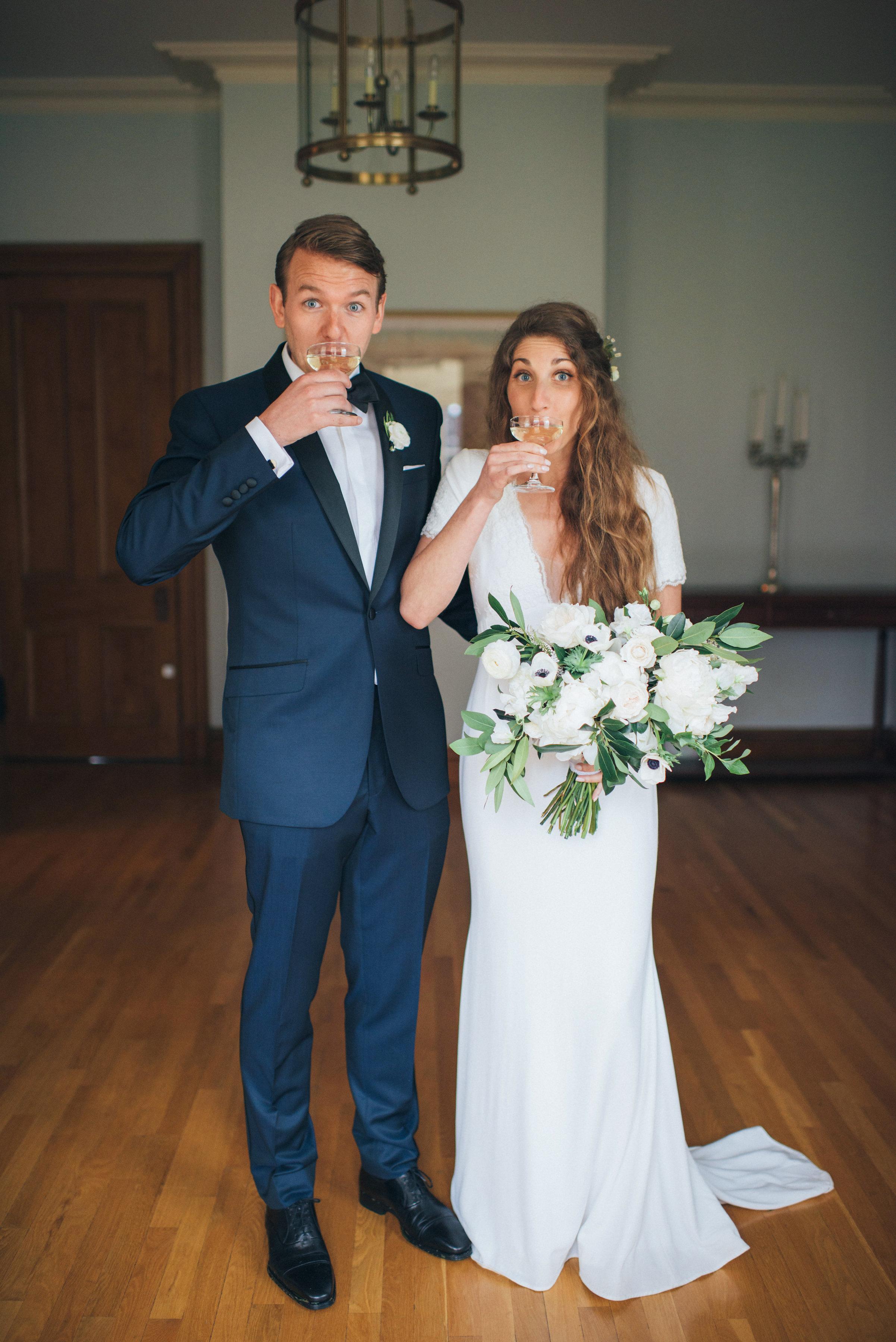 bride groom sip champagne in wedding attire