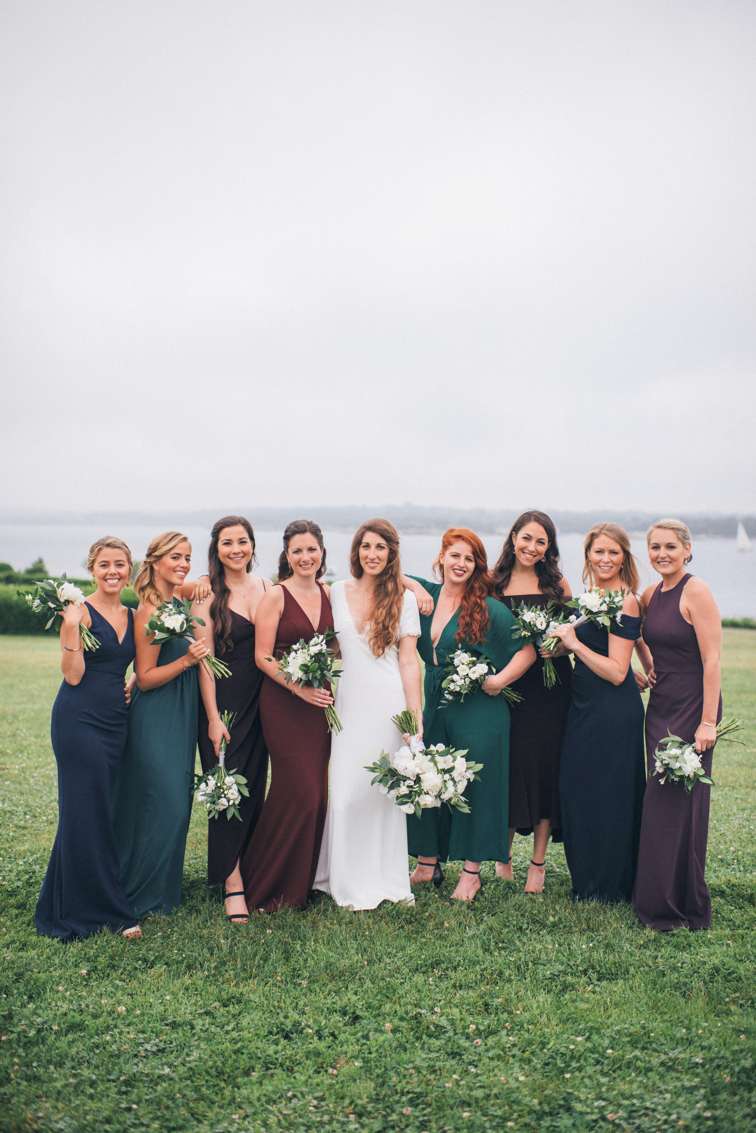 bride and bridemaids pose lakeside backdrop red green dresses