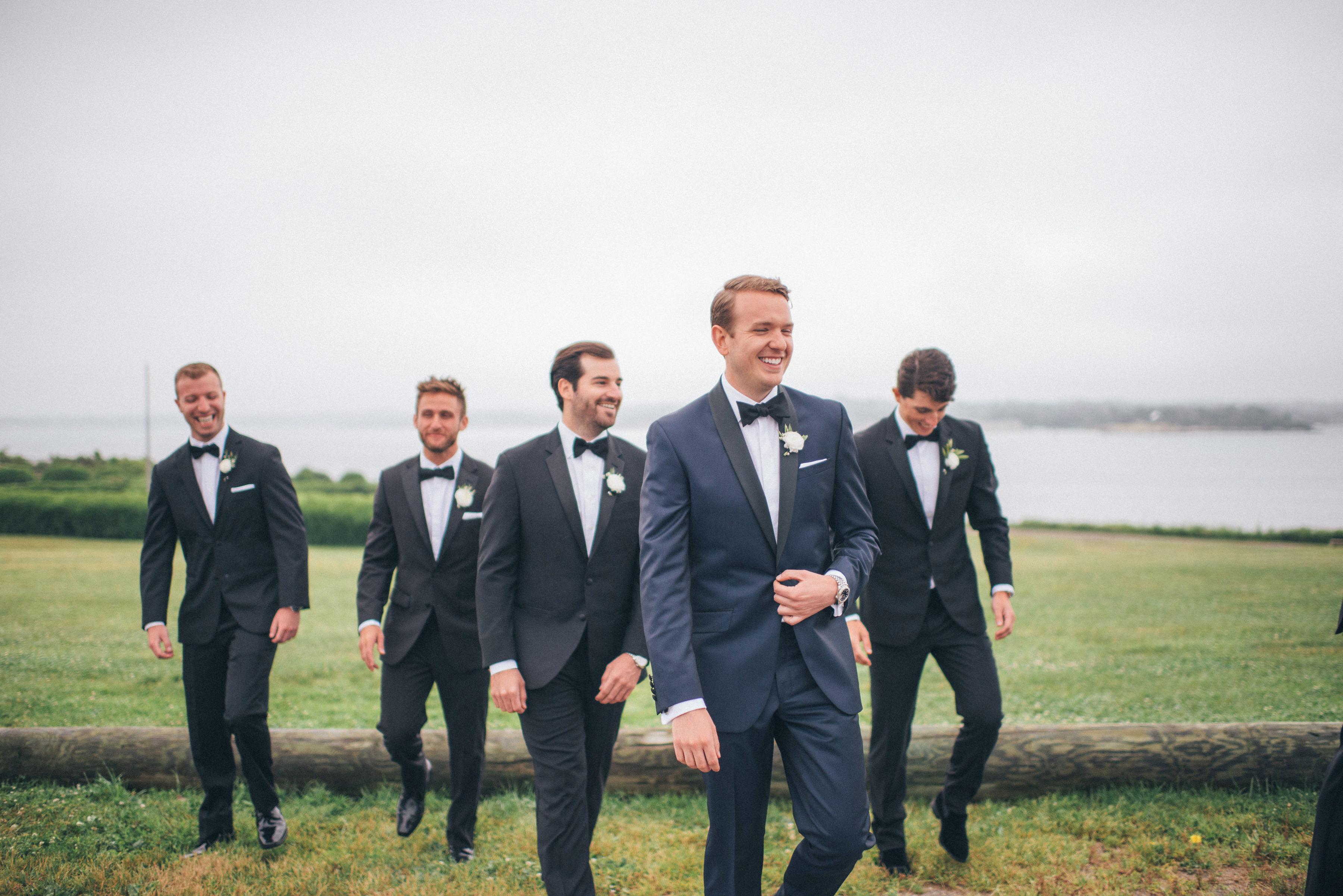 groom and groomsman walking near lake