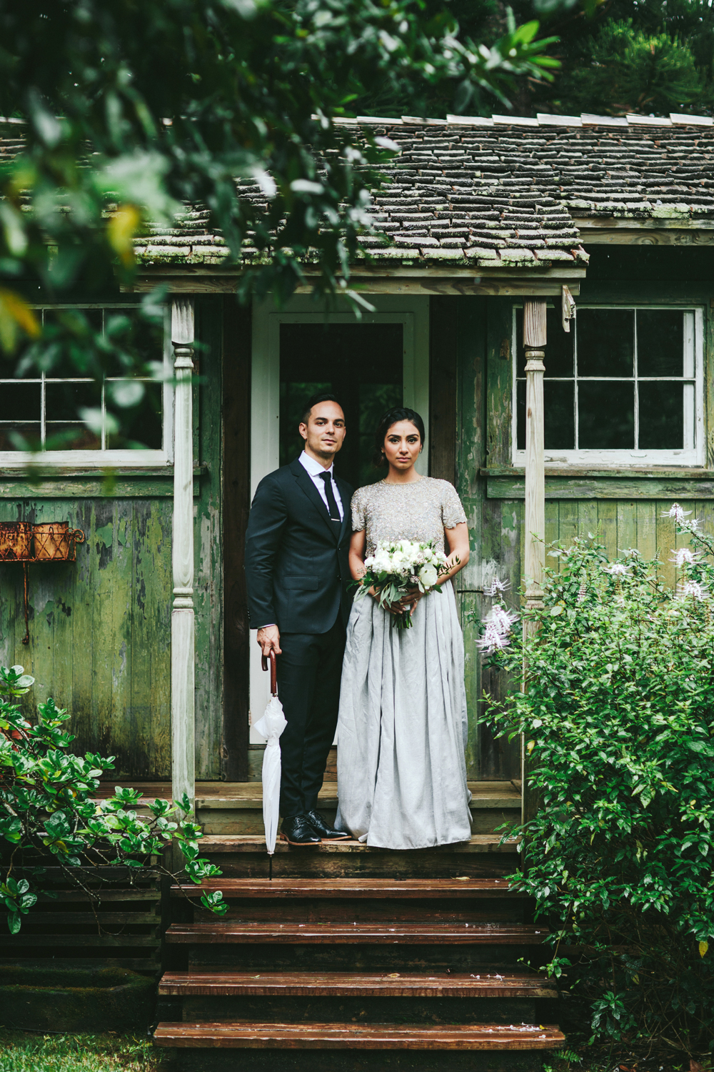 elopement outfit inspiration couple standing outside of green cottage
