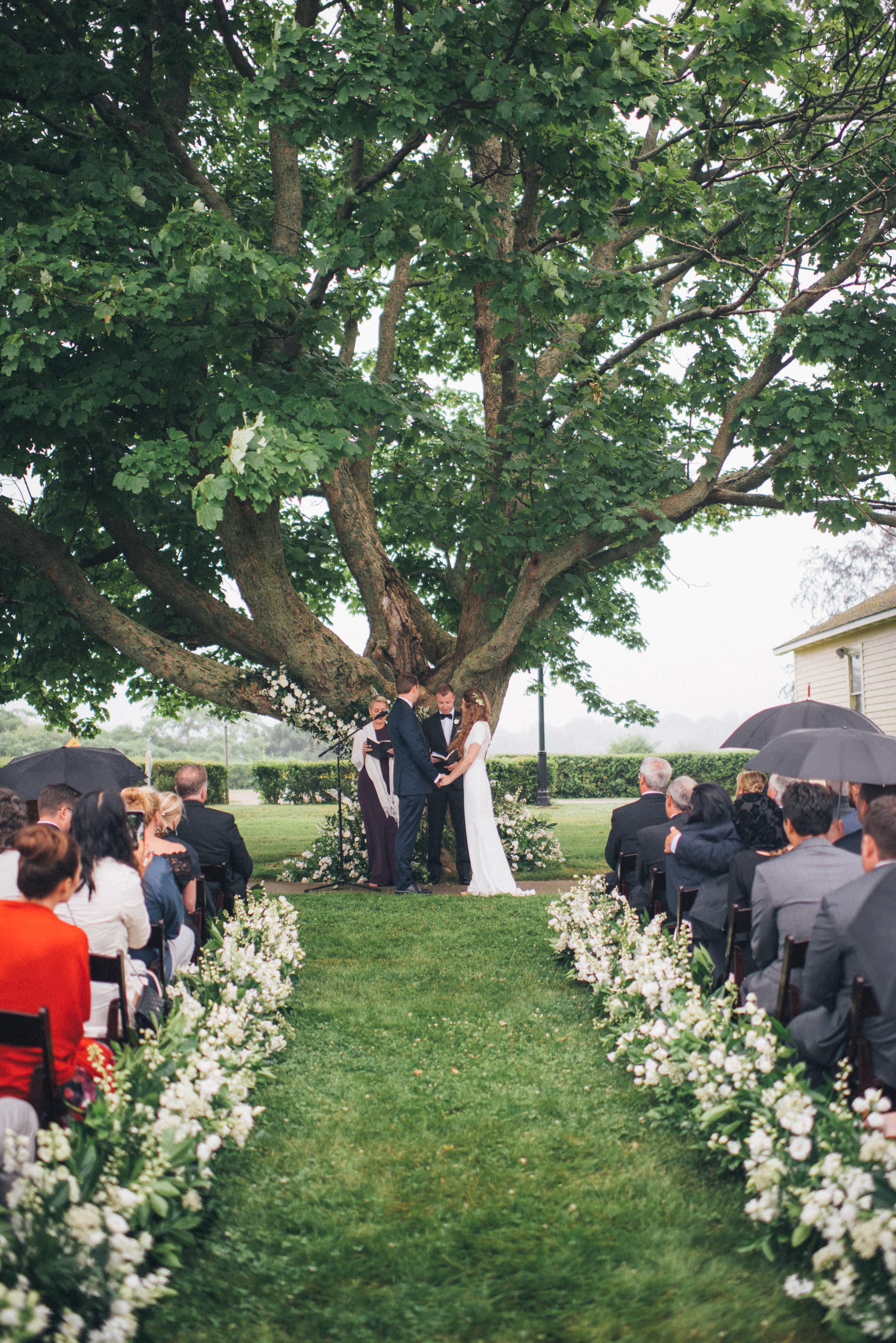 outdoor wedding ceremony below tree guests holding umbrellas