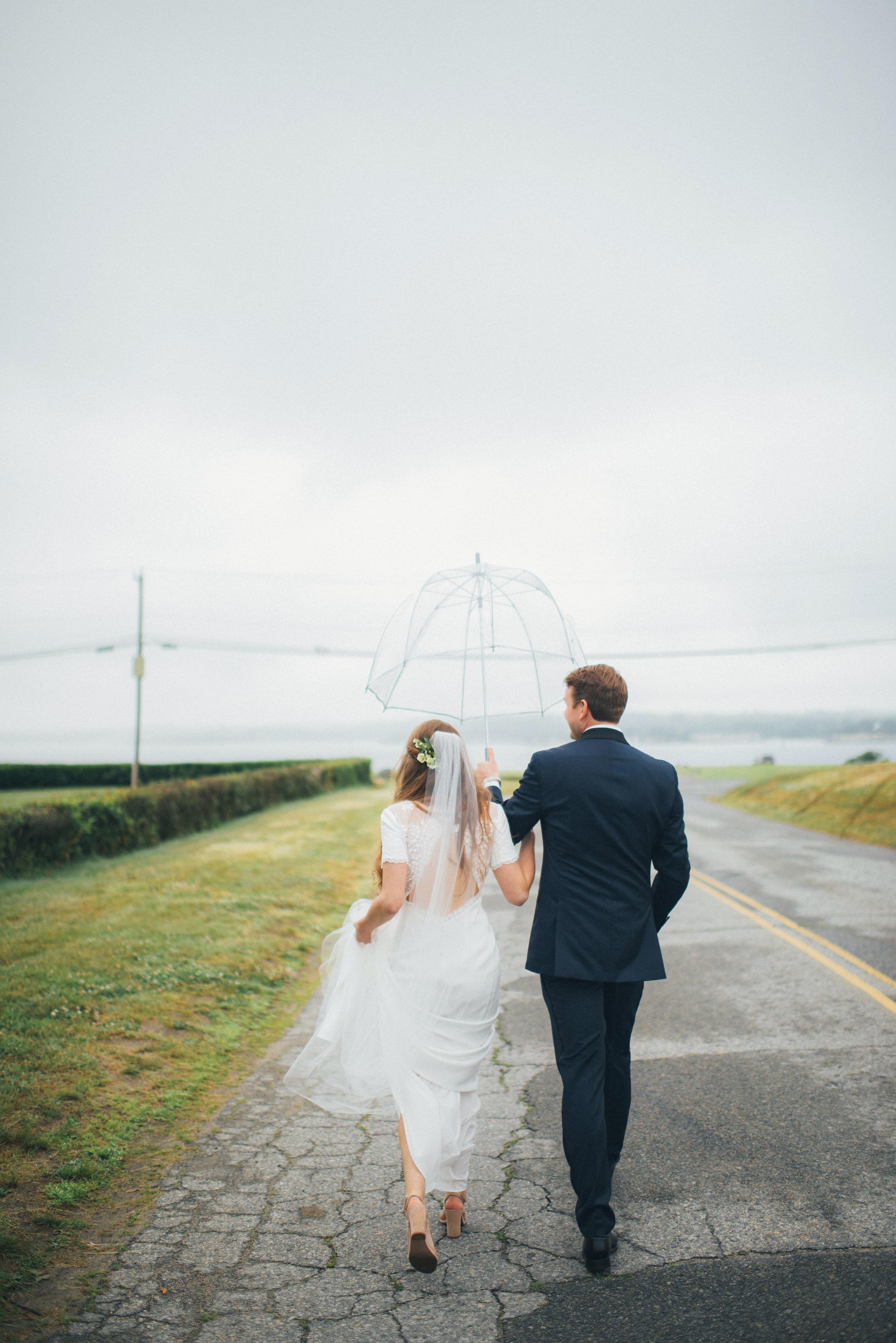 bride groom walk lake view road with umbrella