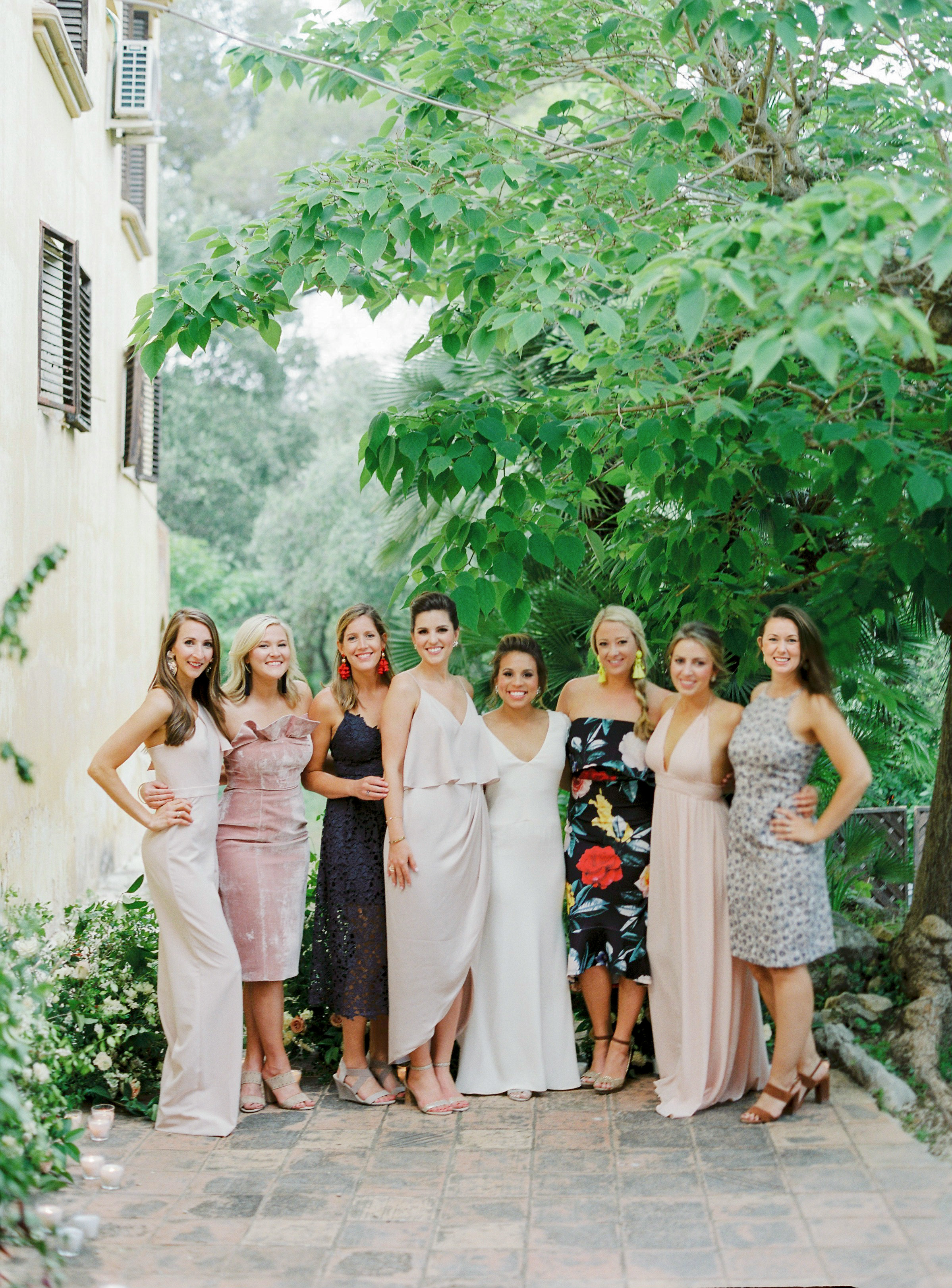 wedding guests pose with bride outdoors