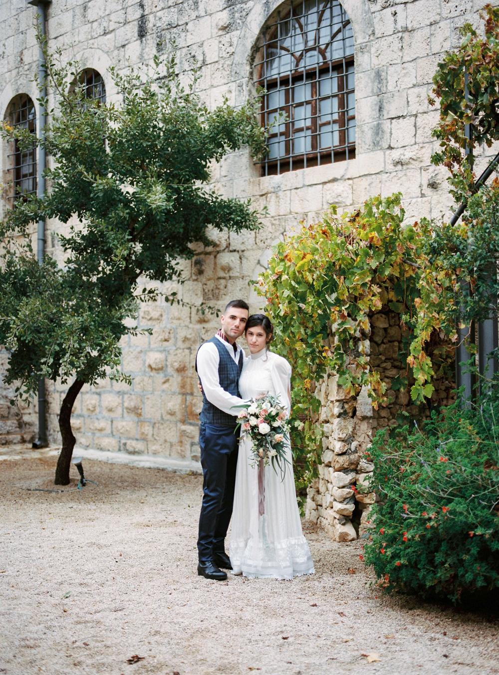bride and groom in victorian attire outside of castle venue