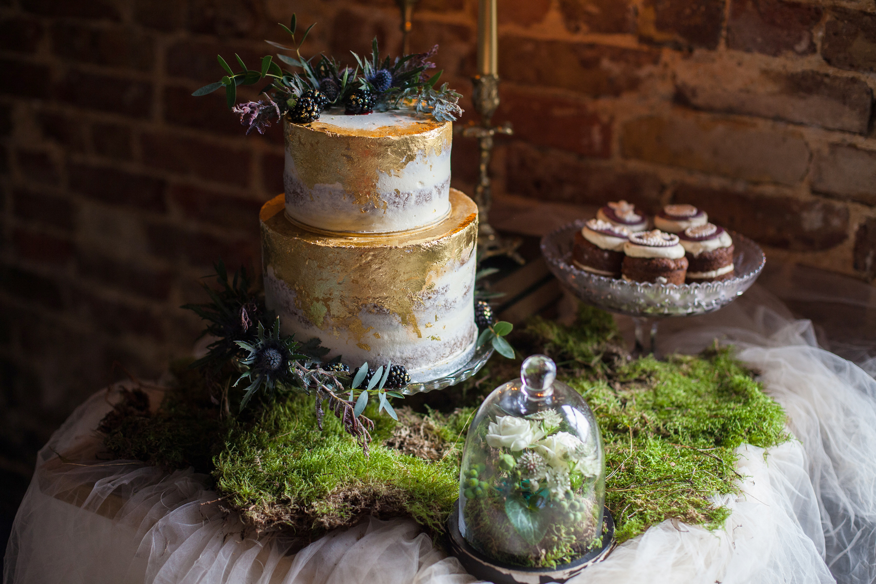 dessert table with gold wedding cake and moss decor