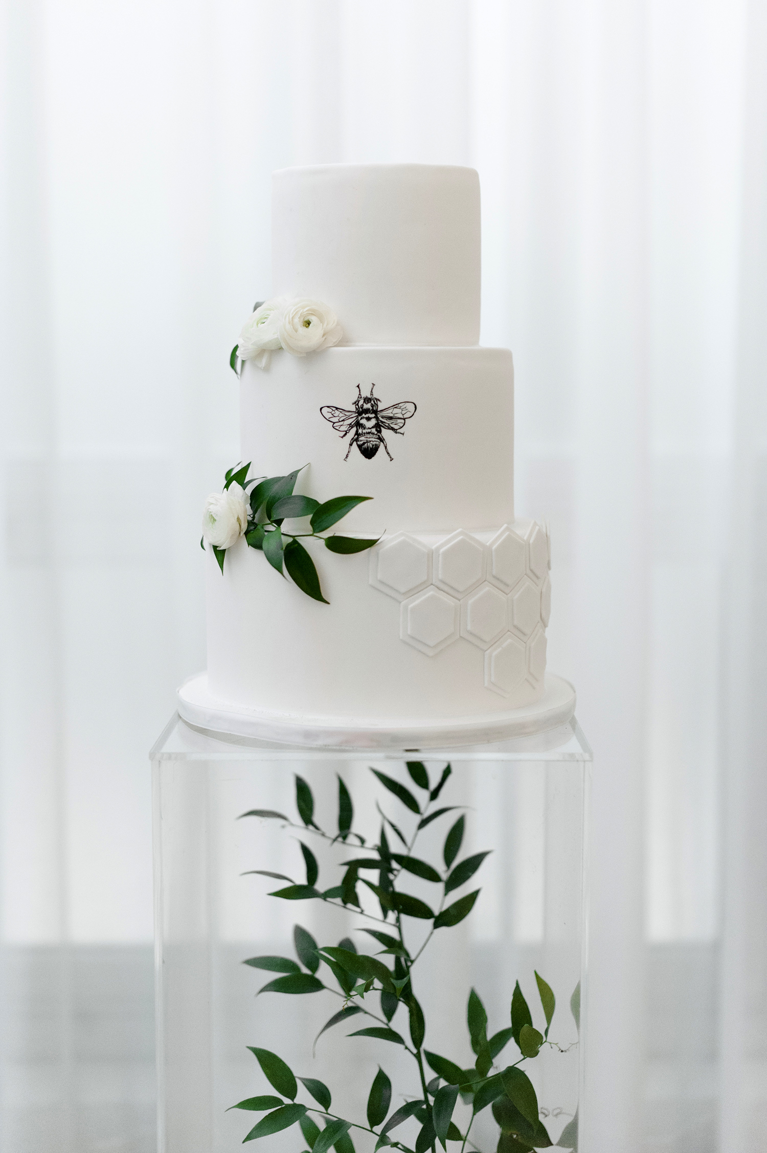bee wedding ideas cake on tall stand with greenery design