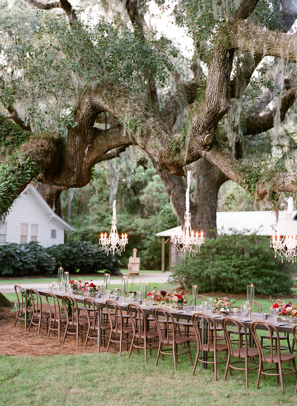 long outdoor dinner table below chandeliers hanging from tree