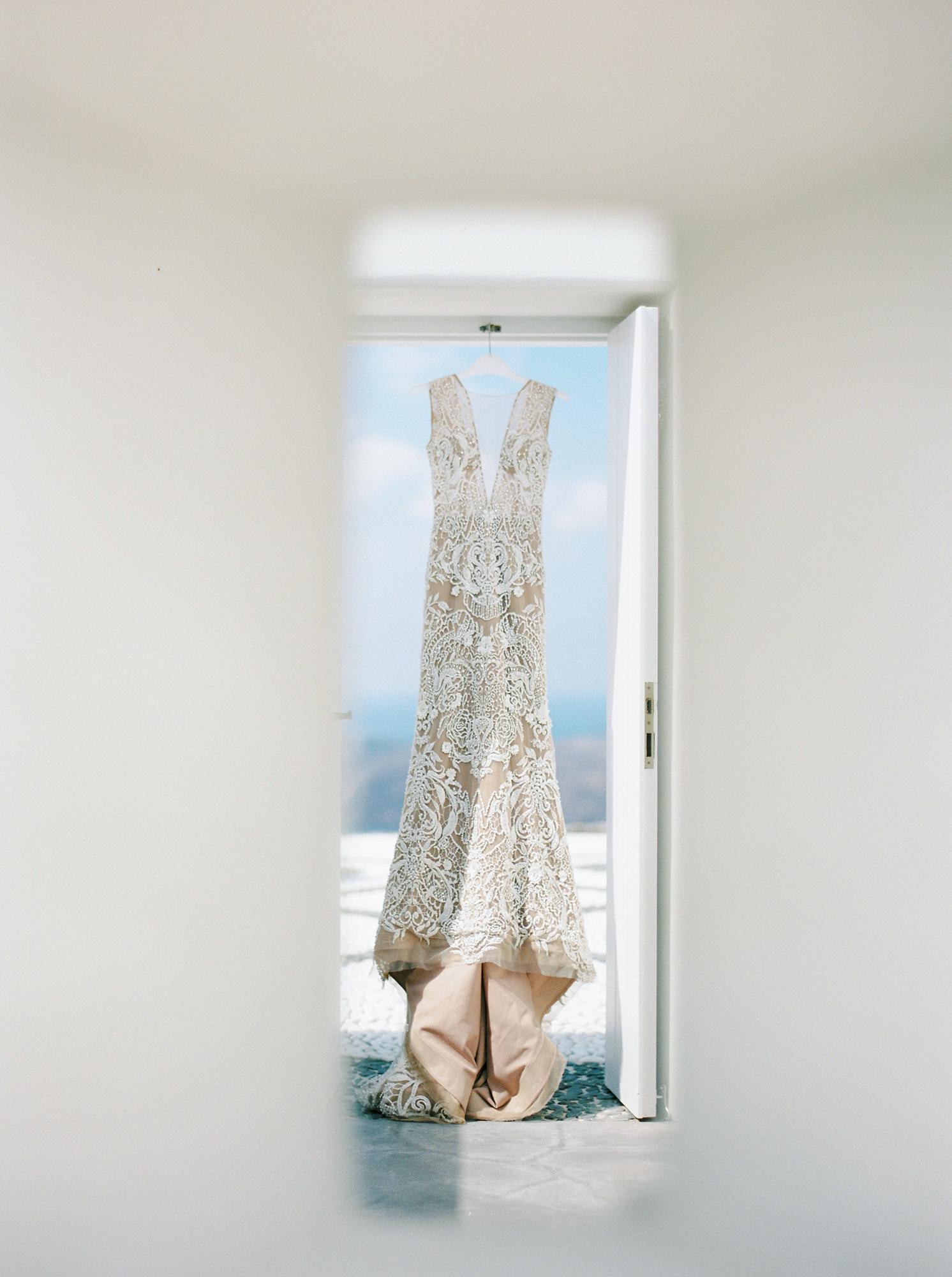 angie prayogo wedding bride wedding dress hanging in doorway