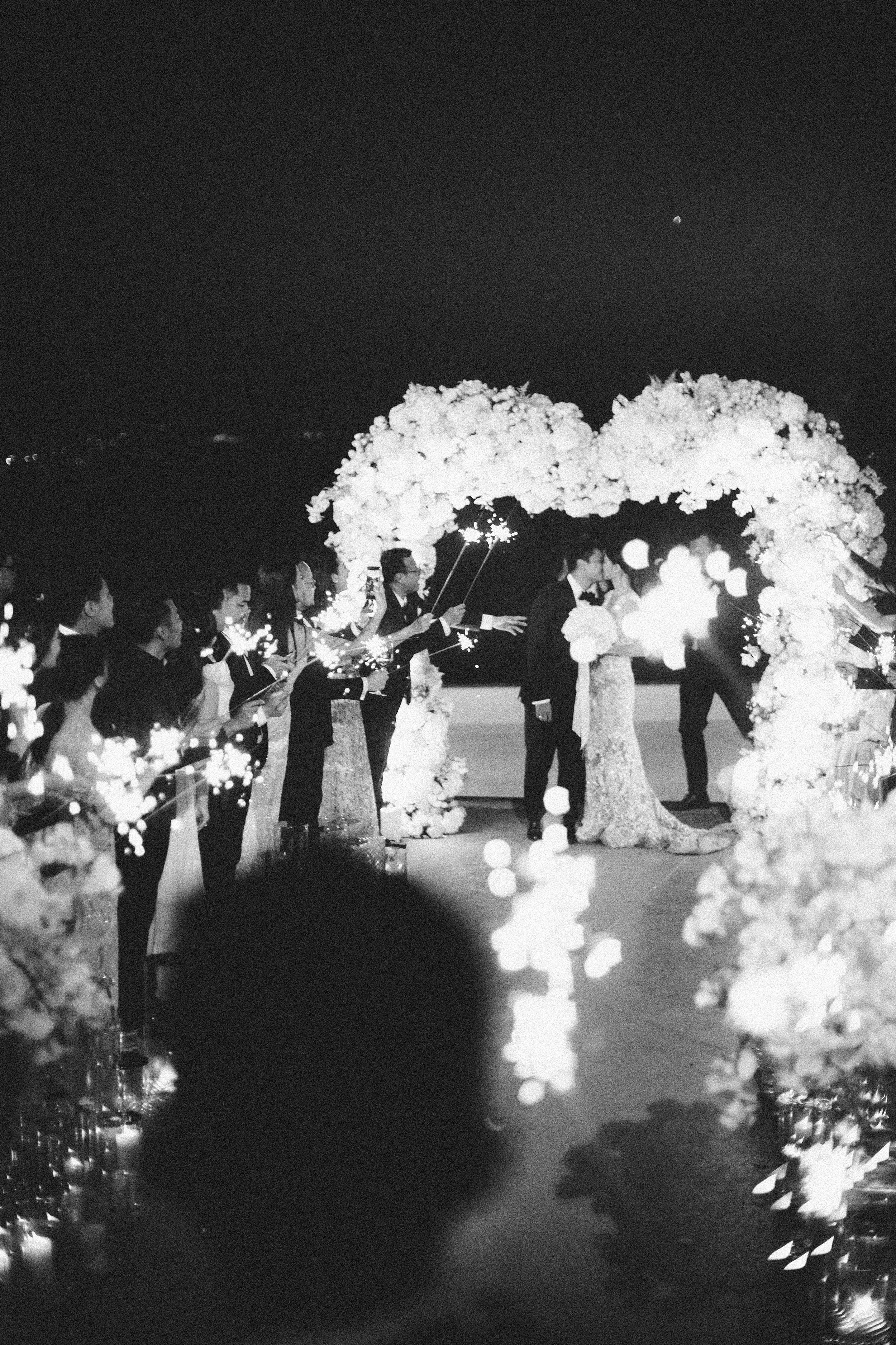 angie prayogo greece wedding sparklers couple kiss under arch