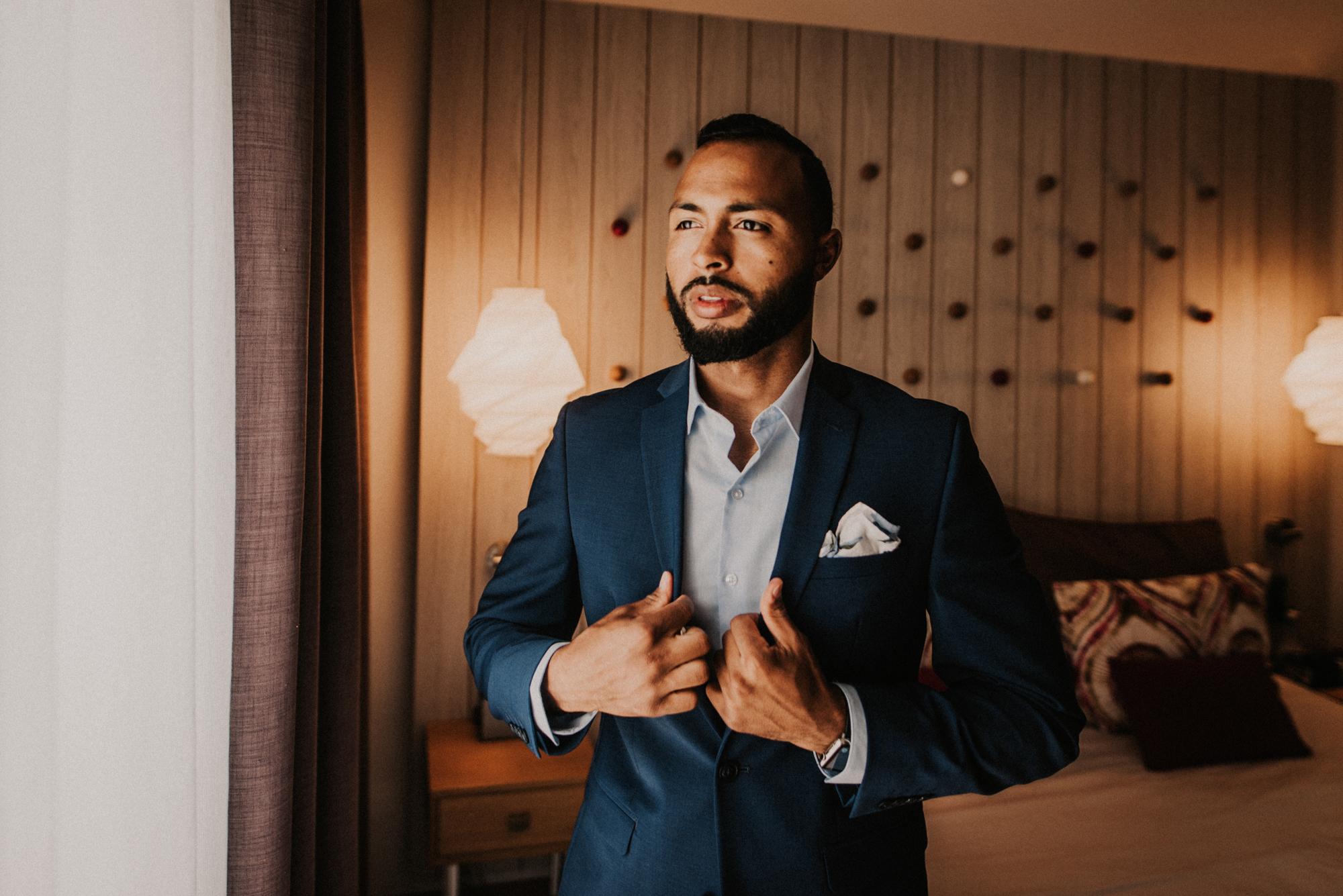groom stands posing in blue suit