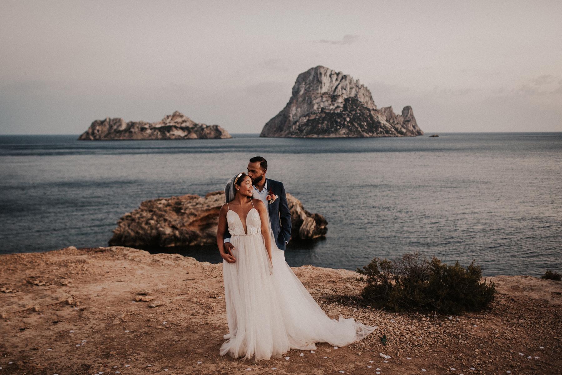 couple poses next to island ceremony location