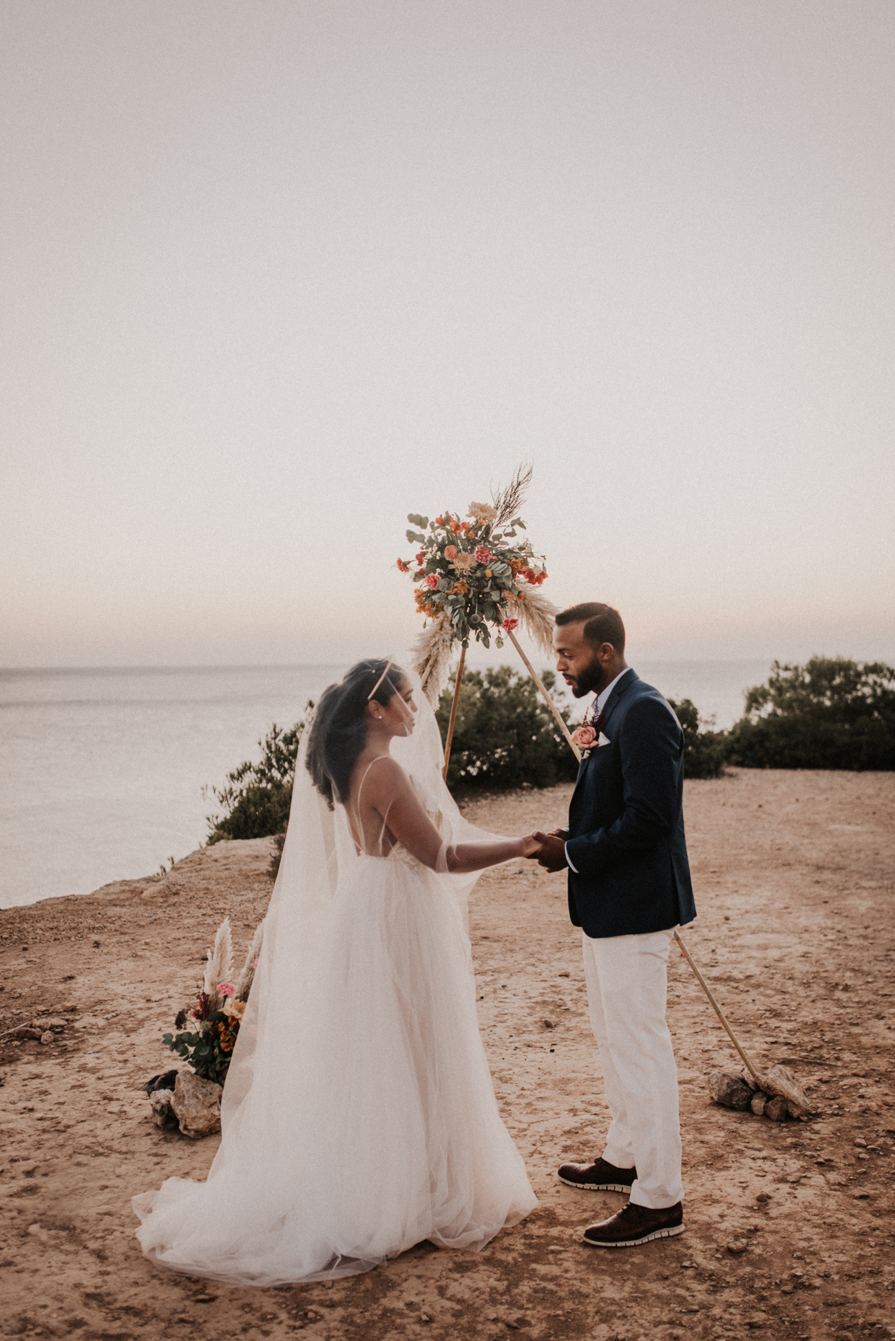 couple stands holding hands by floral arch