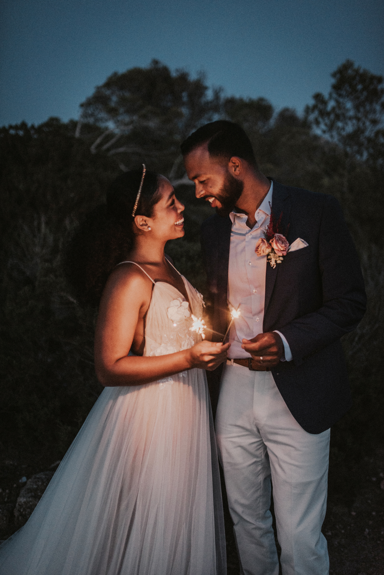 couple faces each other smiling while holding sparklers