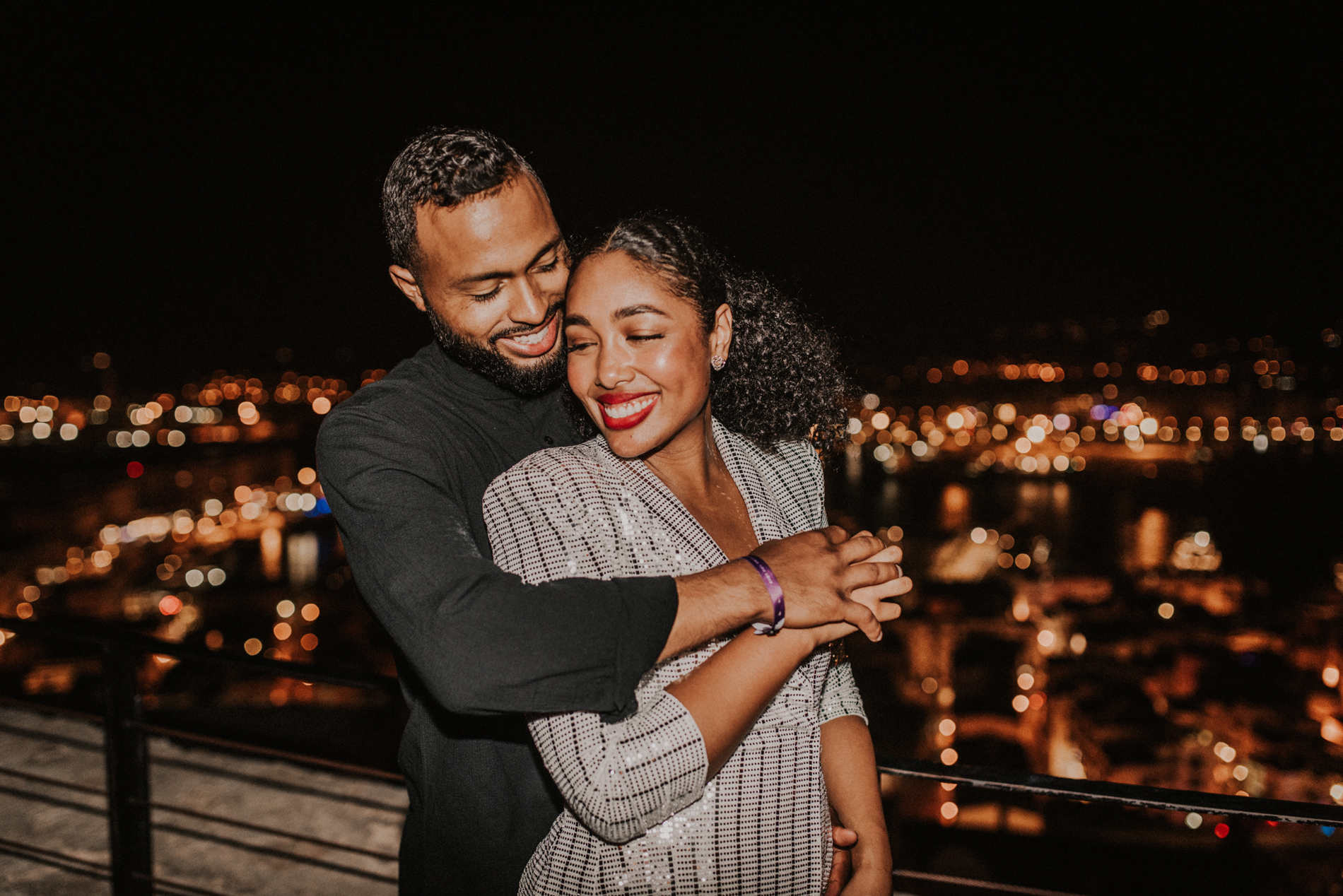 couple stands smiling in front of night time city lights