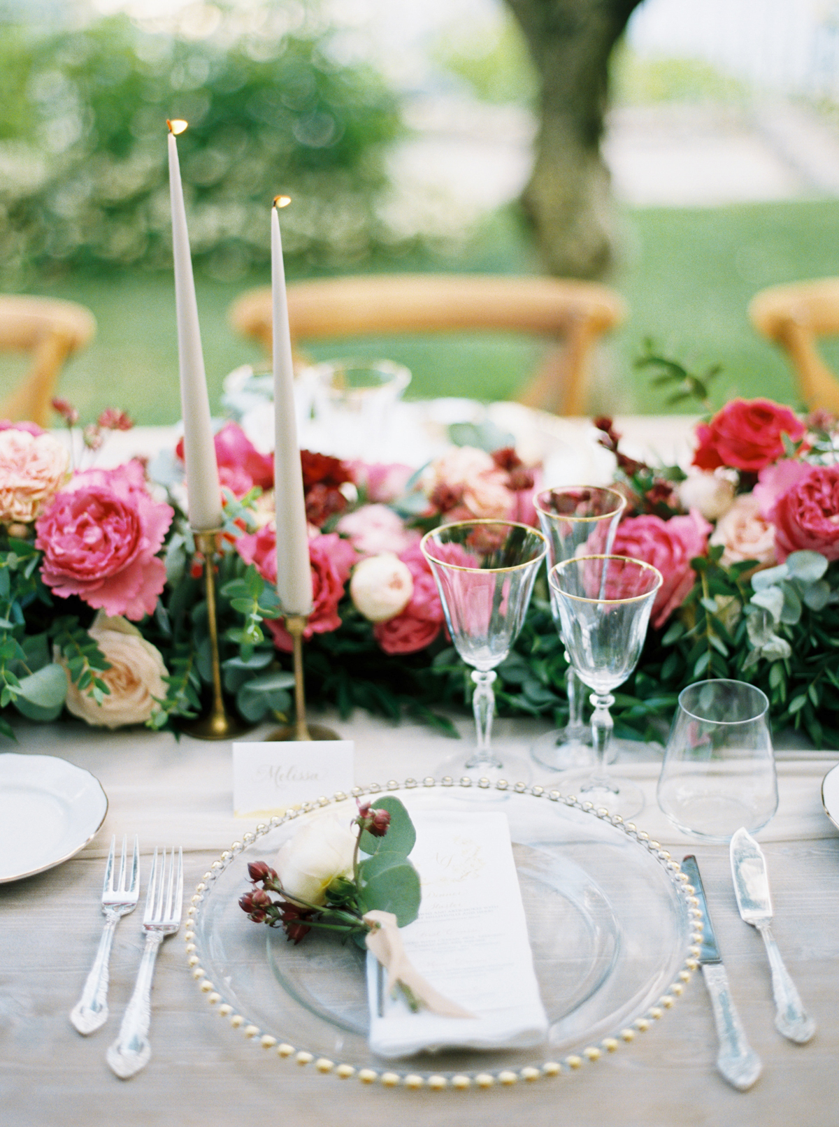 allie and joe italy wedding place setting with gold-rimmed plates topped with white roses