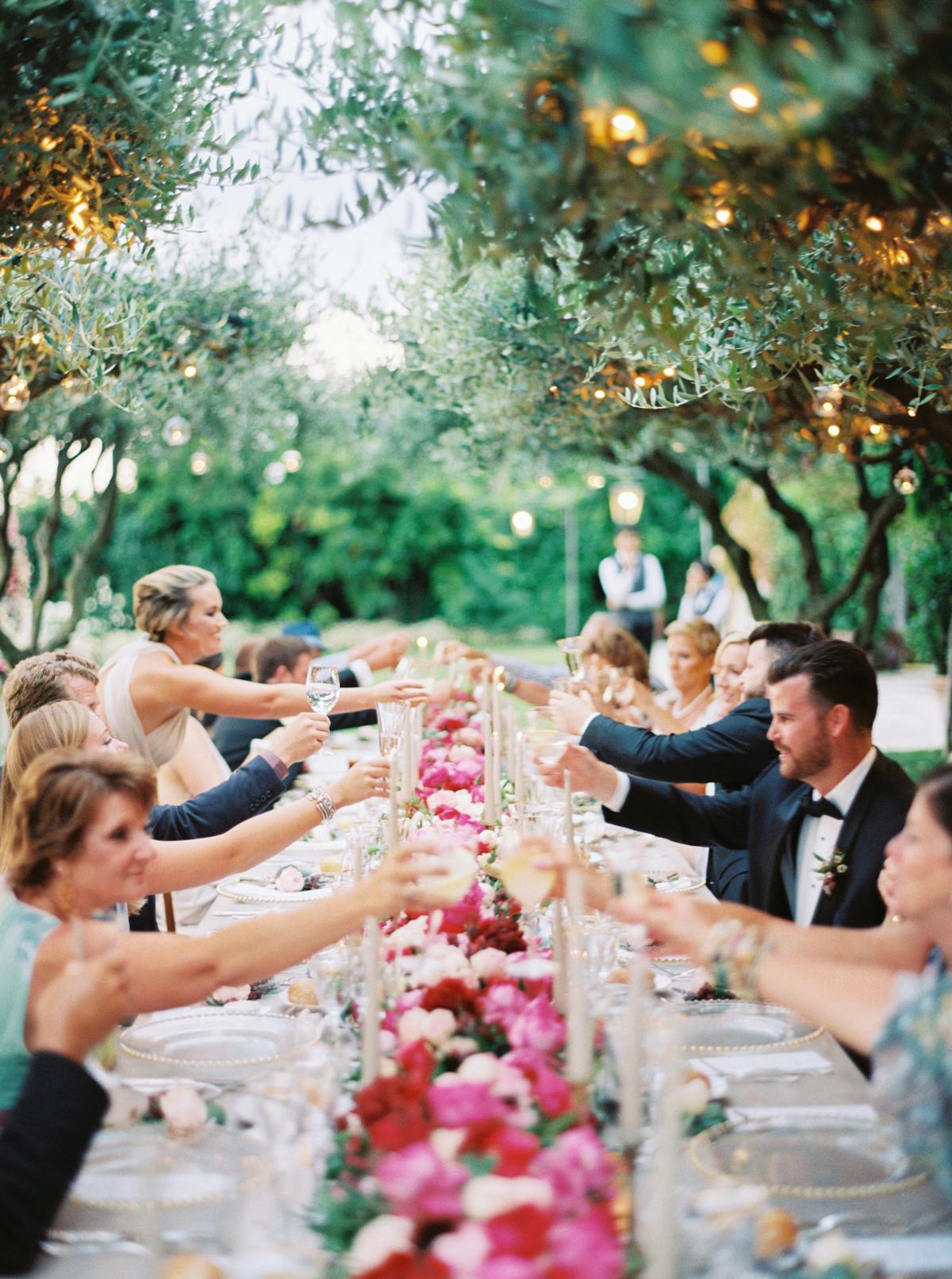 allie and joe italy wedding guests cheersing