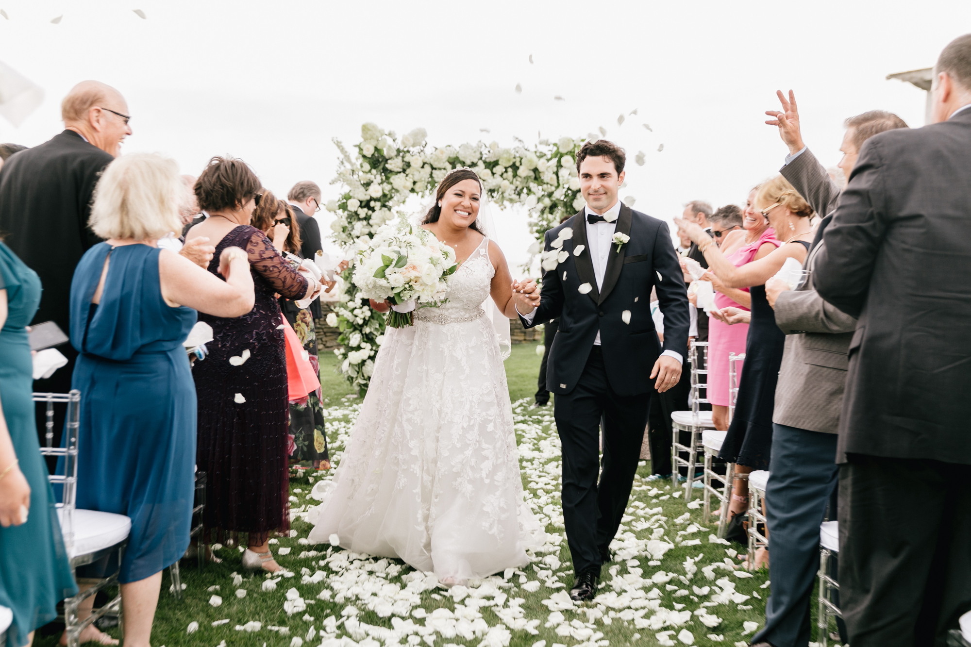 guests throwing white flower petals during wedding recessional