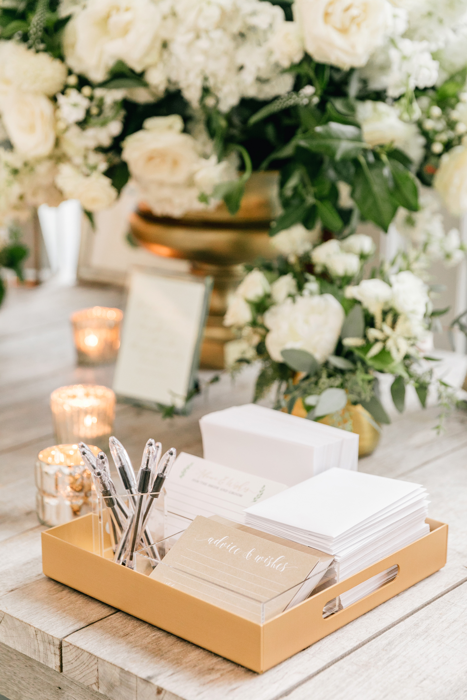 wedding advice cards on wood table with candles and white roses