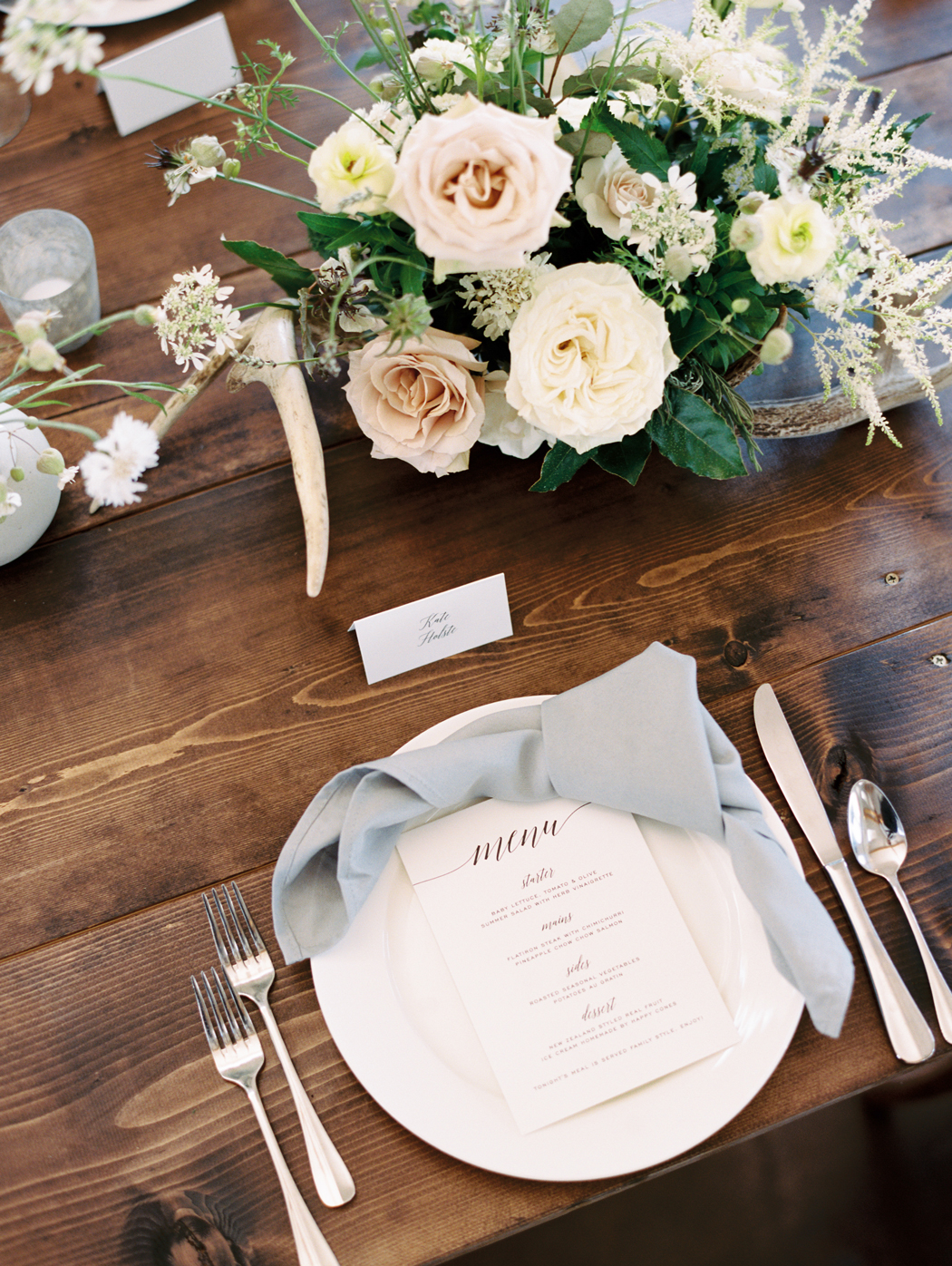 white dinnerware on wood farm tables with floral centerpieces