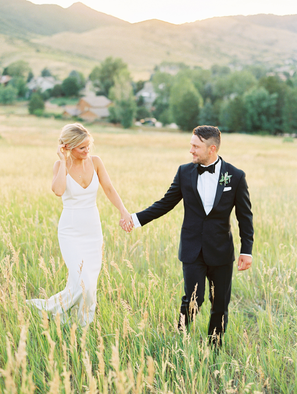 bride and groom hold hands in prairie field outdoors