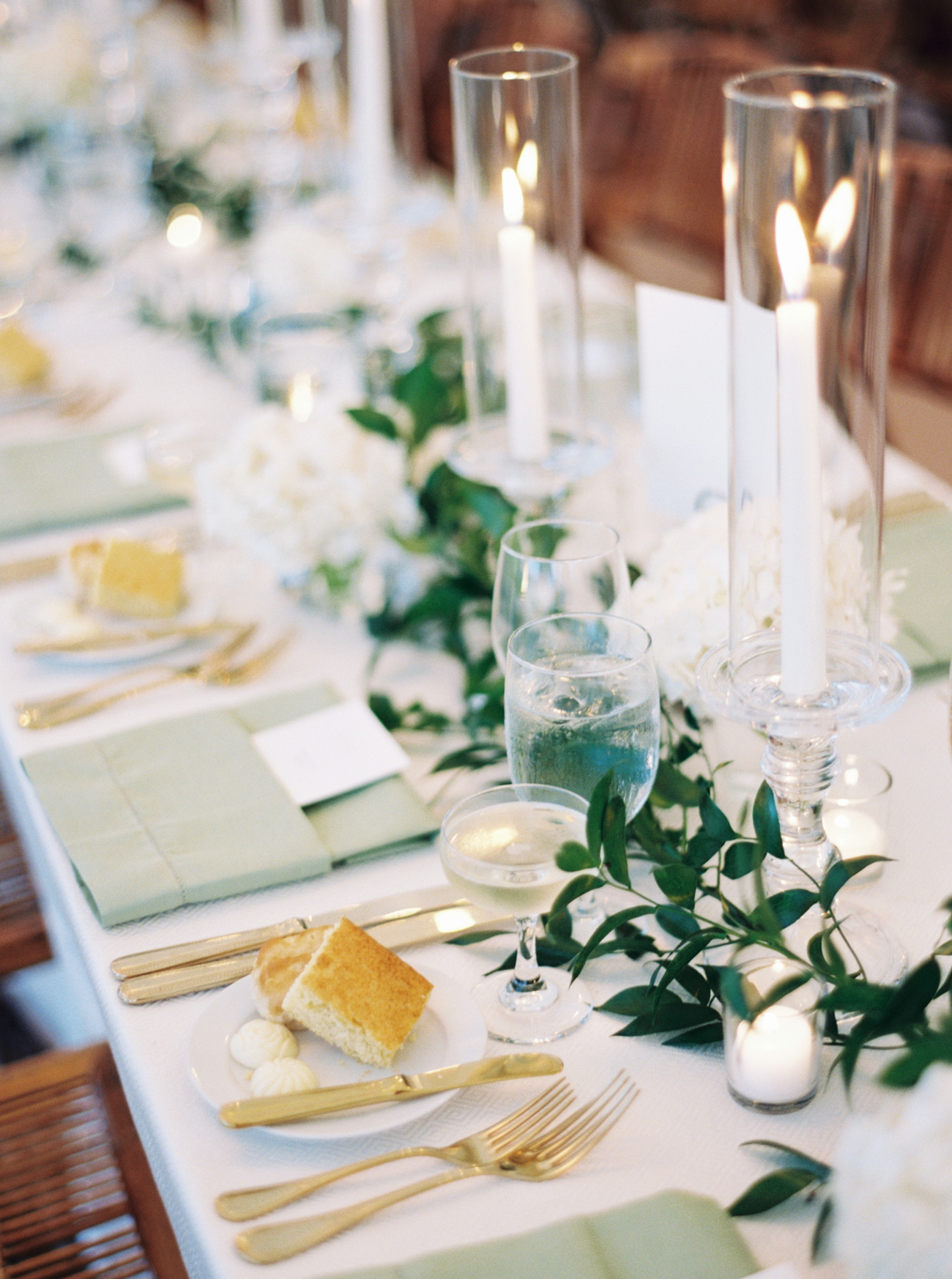 mix of white and green table linens, candles with simple white and gold tableware