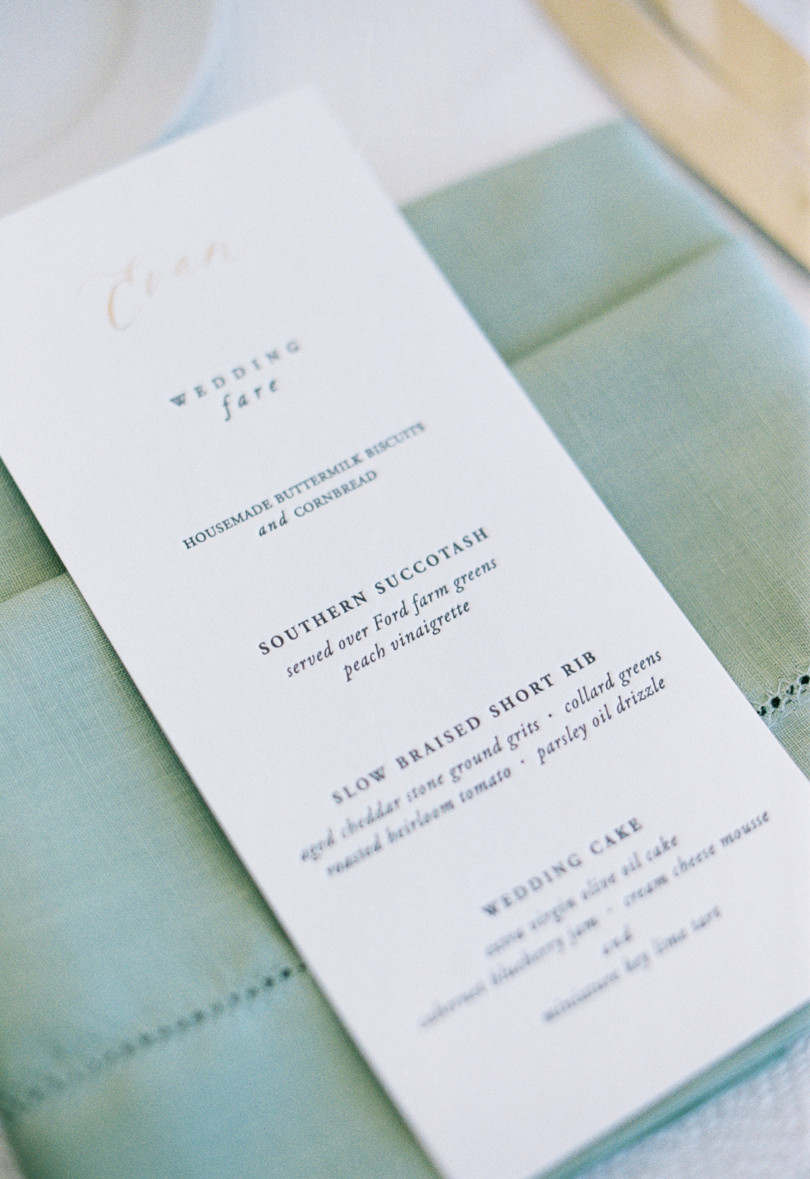white stationary menu with black type and custom gold calligraphy stamp of guests name