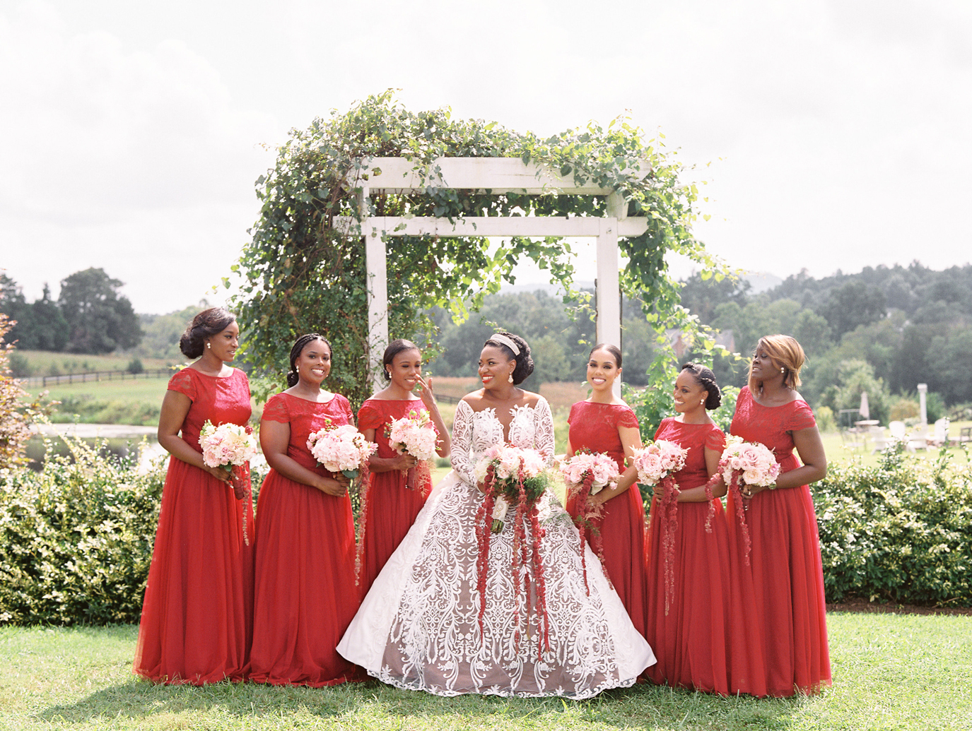 bride in wedding dress with bridesmaids in long red dresses