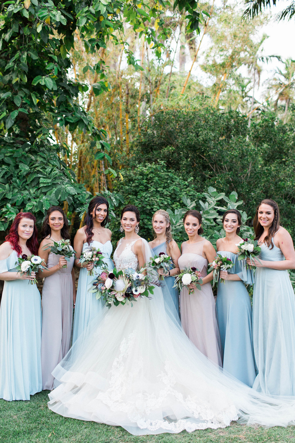 bride with bridesmaids in complimentary-colored dusty blue gowns