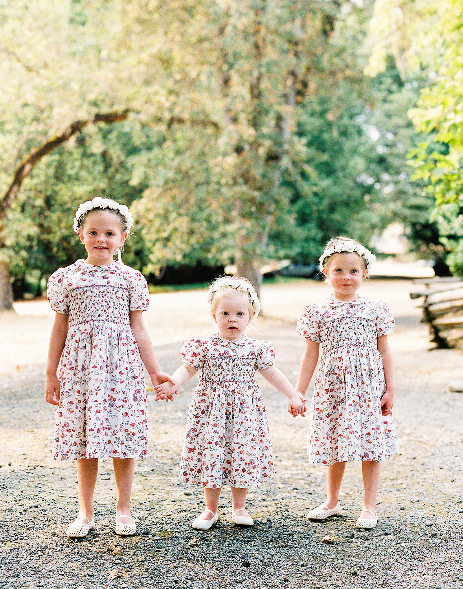 three flower girls wearing floral dresses