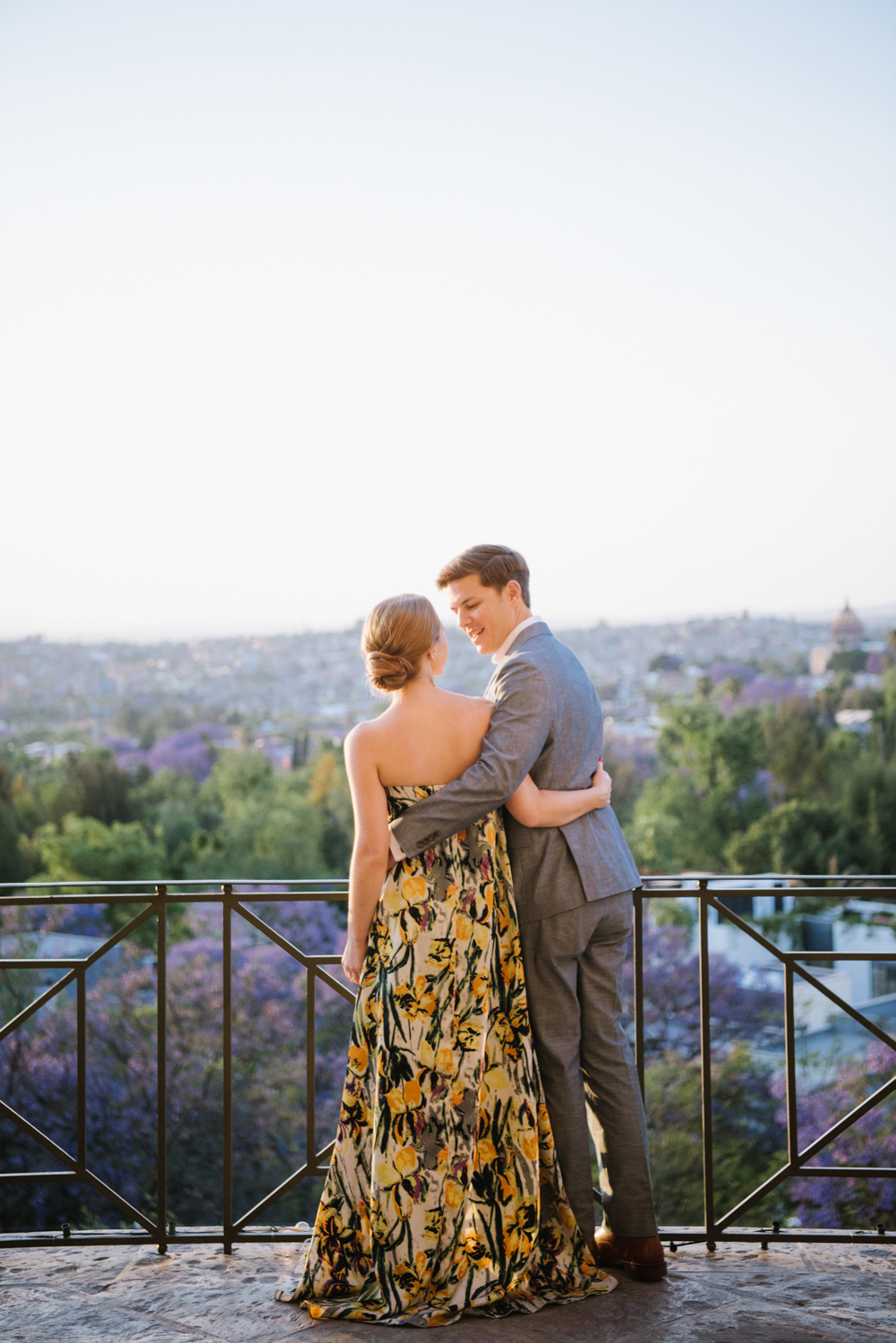 couple looking over terrace during rehearsal dinner