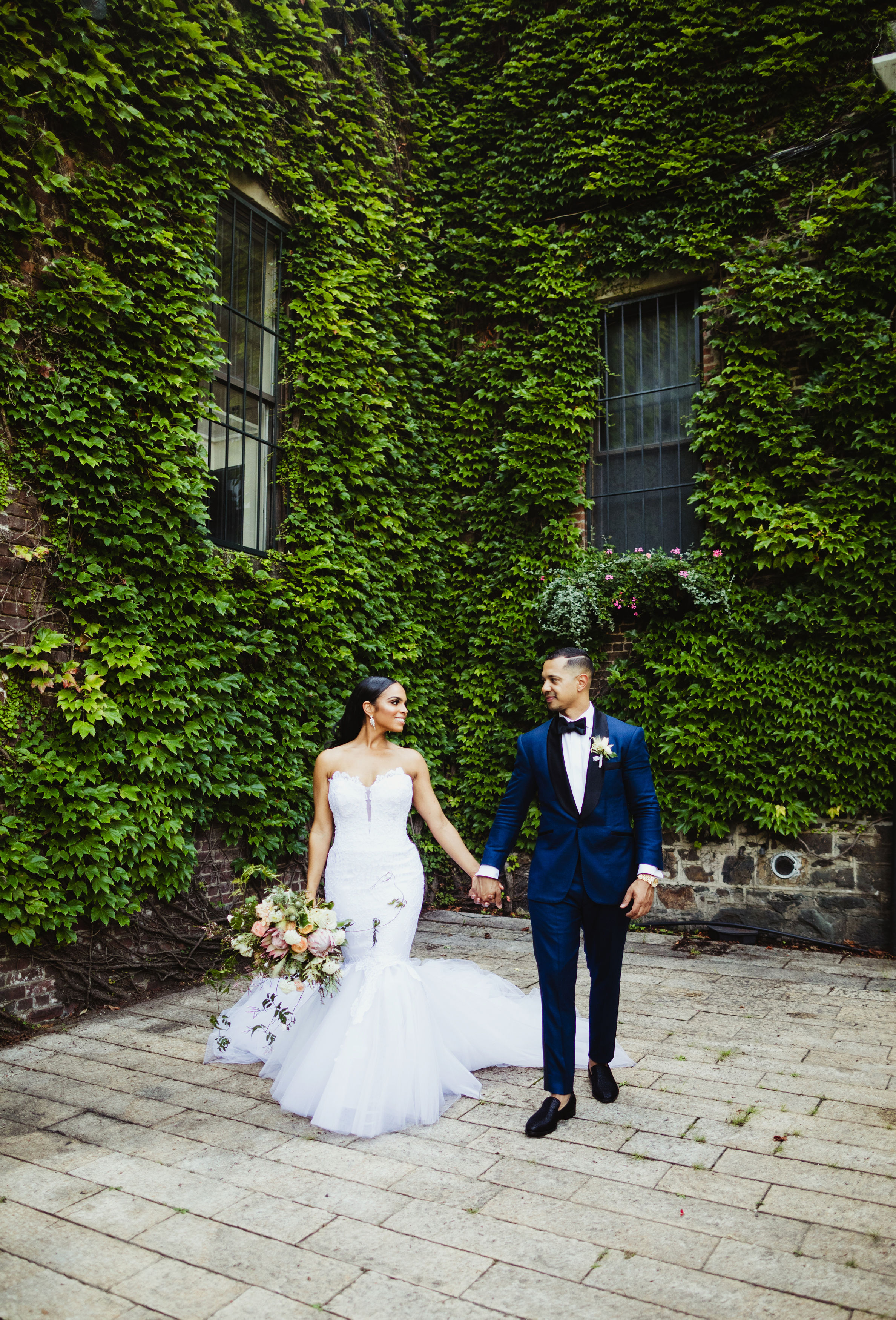 bride and groom walking together against greenery backdrop